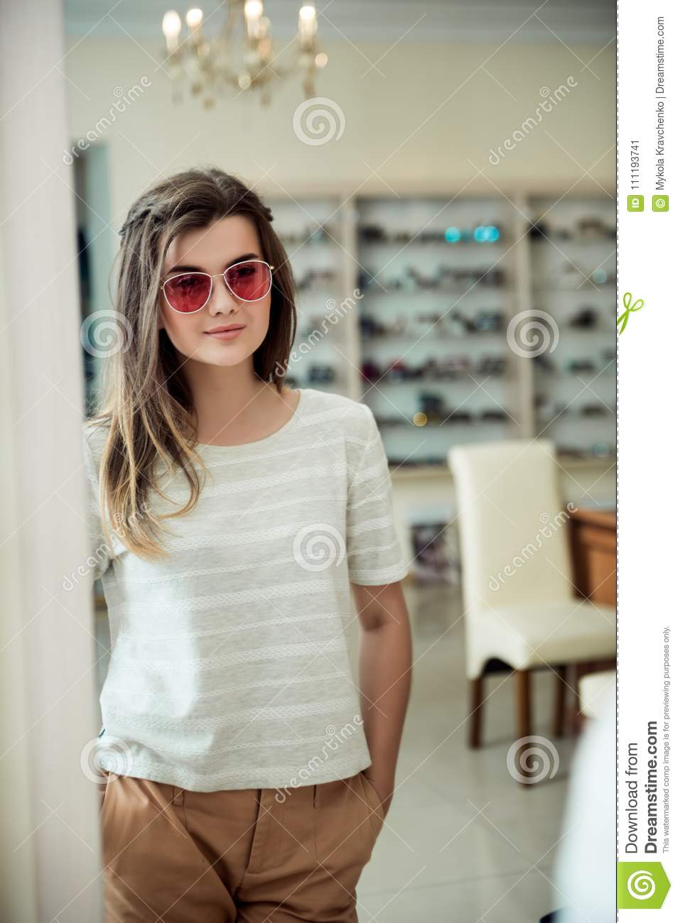 Horizontal portrait of charming young european female customer standing in optician store, trying stylish pair of