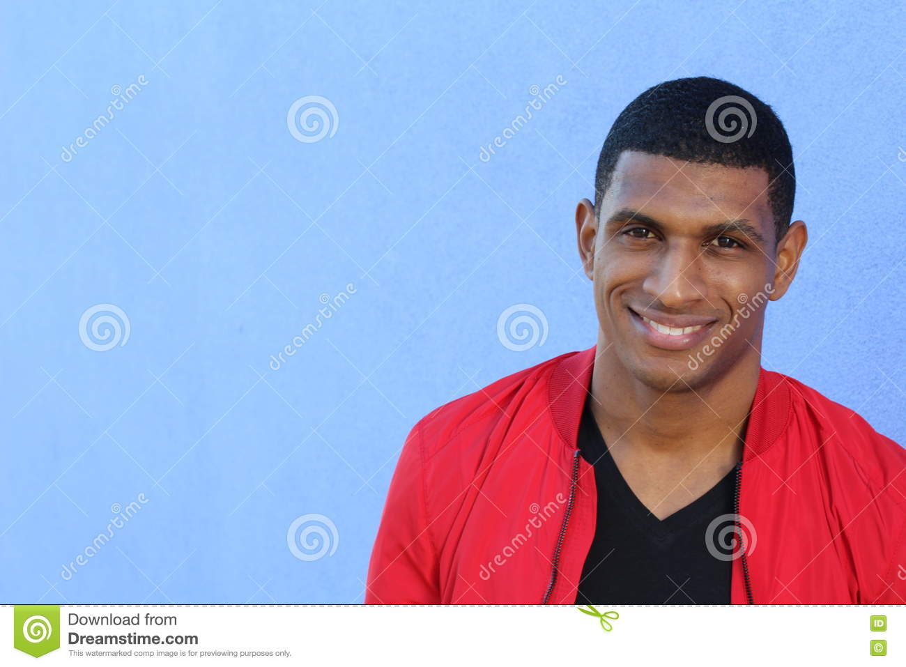 Horizontal portrait of a handsome young african man smiling on blue background.