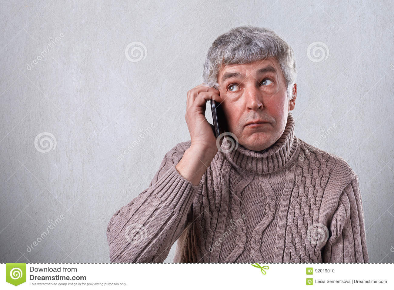 A horizontal portrait of mature man with gray hair and wrinkles dressed in warm sweater holding mobile phone on his ear looking as
