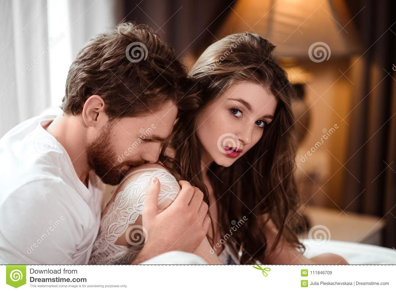 Horizontal shot of atrractive male kisses his female lover in shoulder, express love and passion, spend free time at