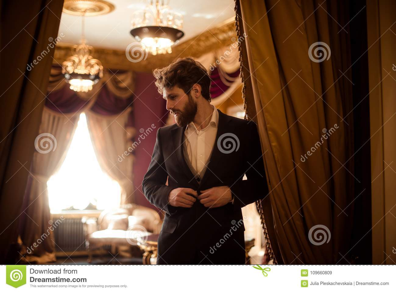 Horizontal shot of bearded male entrepreneur dressed in formal suit, stands in royal room with luxury curtains and