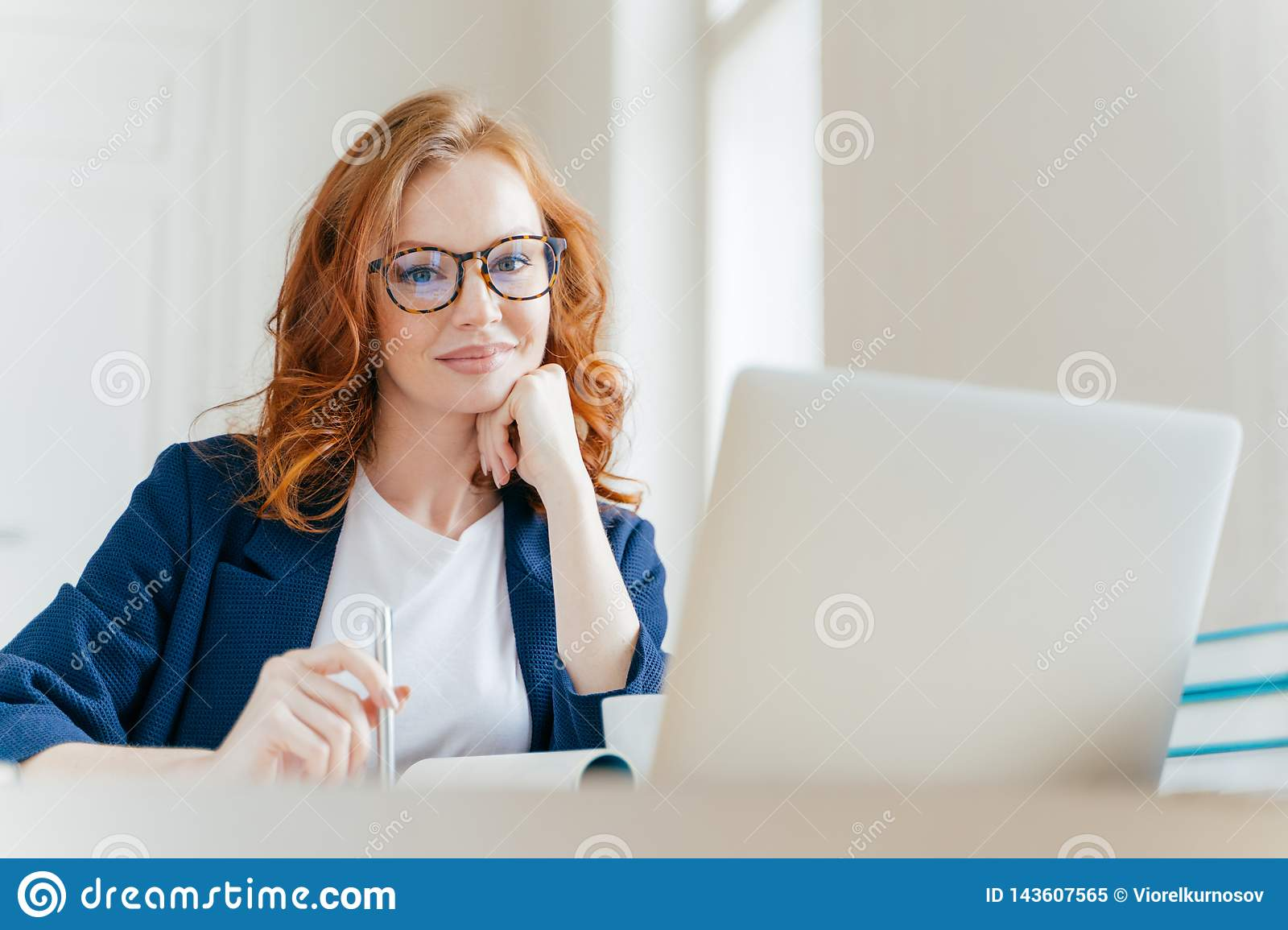 Horizontal shot of pleasant looking successful professional female lawyer learns clients case, works on modern laptop computer,