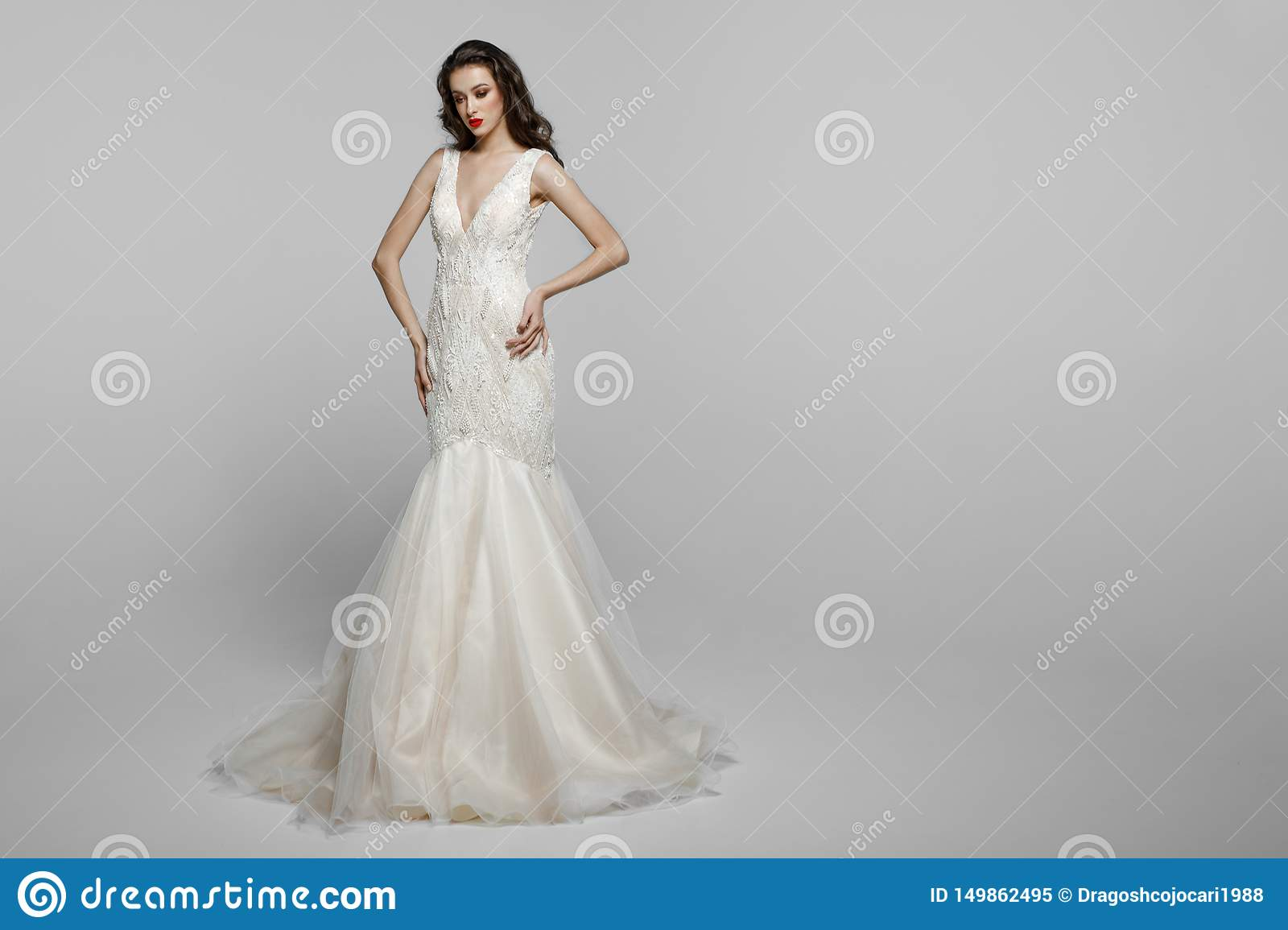 Horizontal view of a beautiful female model with long hair, make up in wendding dress, isolated on a white background.