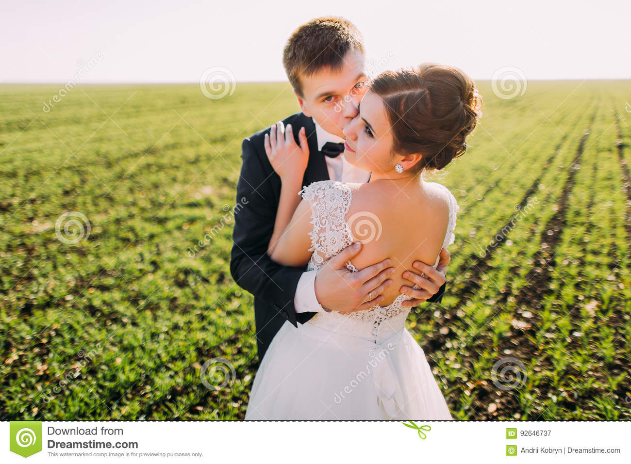 The horizontal view of the bride back kissed by the groom in the cheek at the background of the green field.