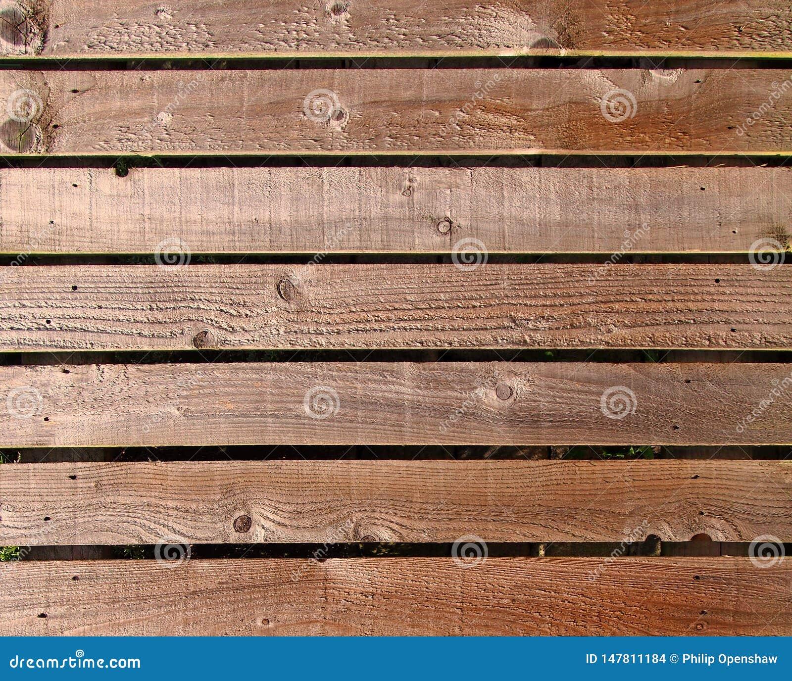 Horizontale raue strukturierte braune Holzbauweiseplanken benutzt als Fechten oder Wände im Freien