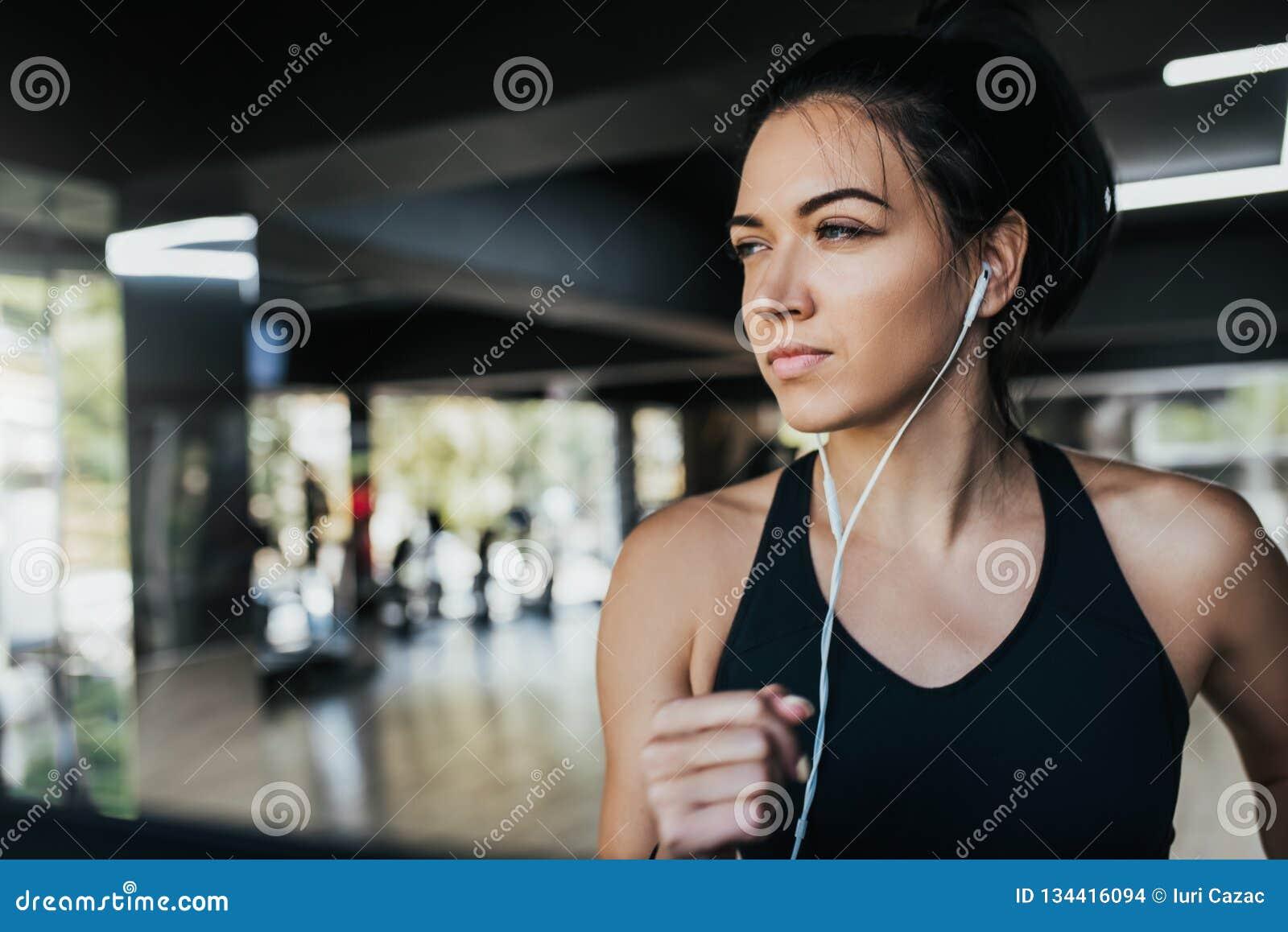 Horizontaler Schuss der hörenden Musik des jungen kaukasischen Frauenläufers auf Kopfhörern beim Laufen in die Turnhalle, tragend
