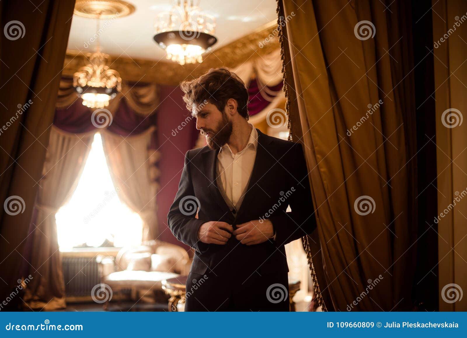 Horizontaler Schuss des bärtigen männlichen Unternehmers kleidete im Gesellschaftsanzug, Stände im königlichen Raum mit Luxusvorh
