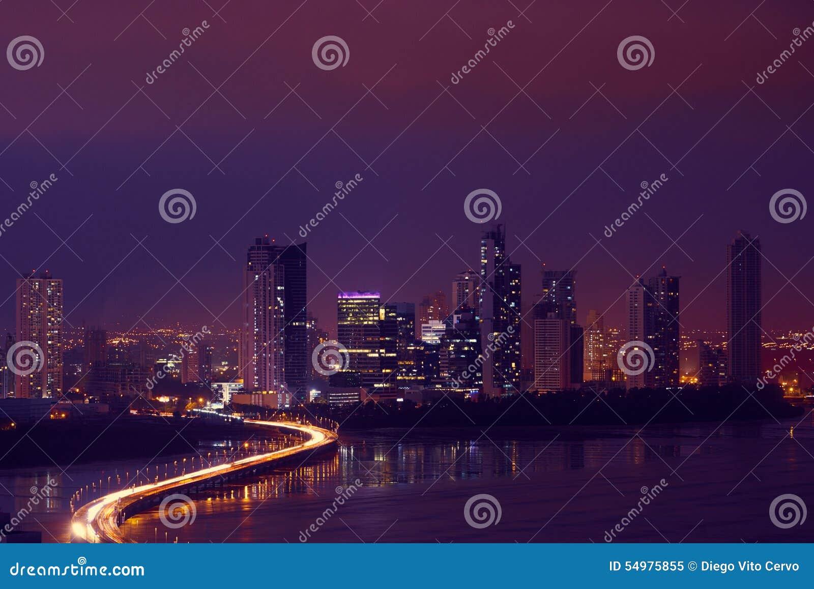 Horizonte de la noche de ciudad de Panamá con tráfico de coche en la carretera