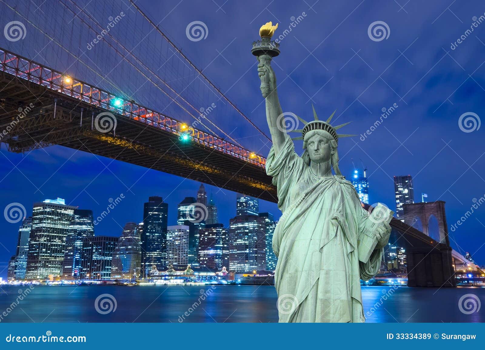 Horizonte y Liberty Statue de Nueva York en la noche, NY, los E.E.U.U.