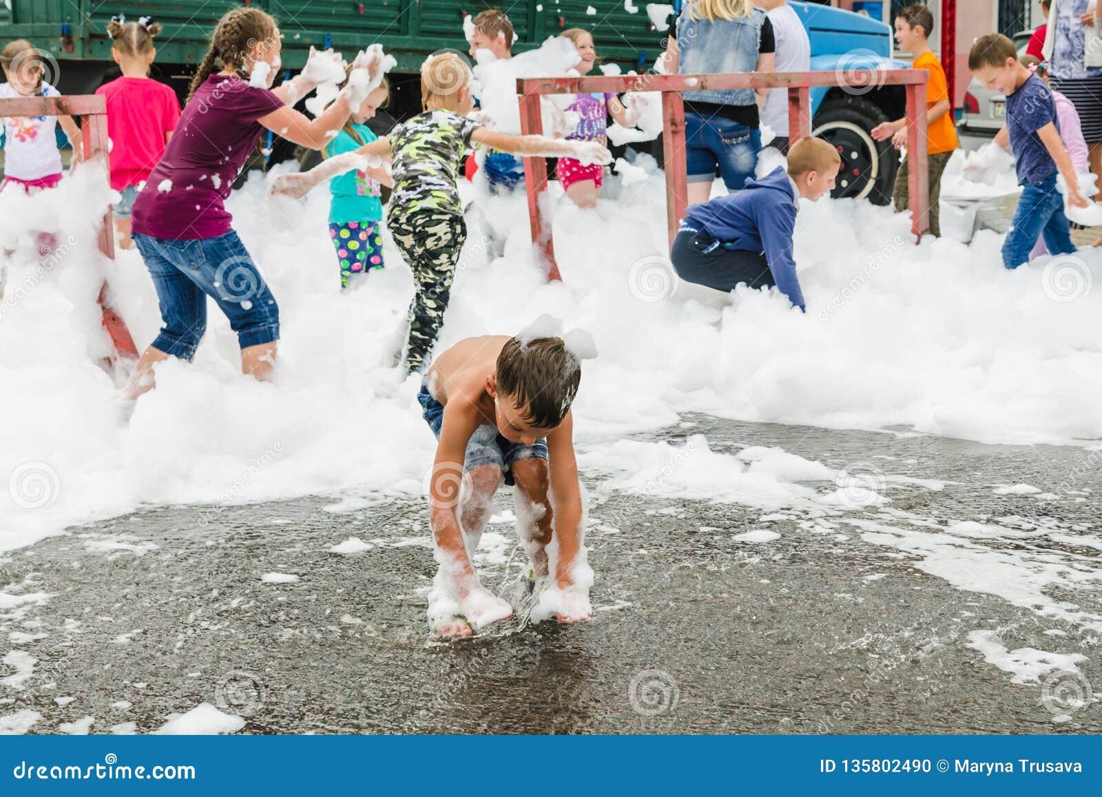 HORKI, БЕЛАРУСЬ - 25-ОЕ ИЮЛЯ 2018: Дети различных возрастов играют с белой пеной в парке на партии в летнем дне