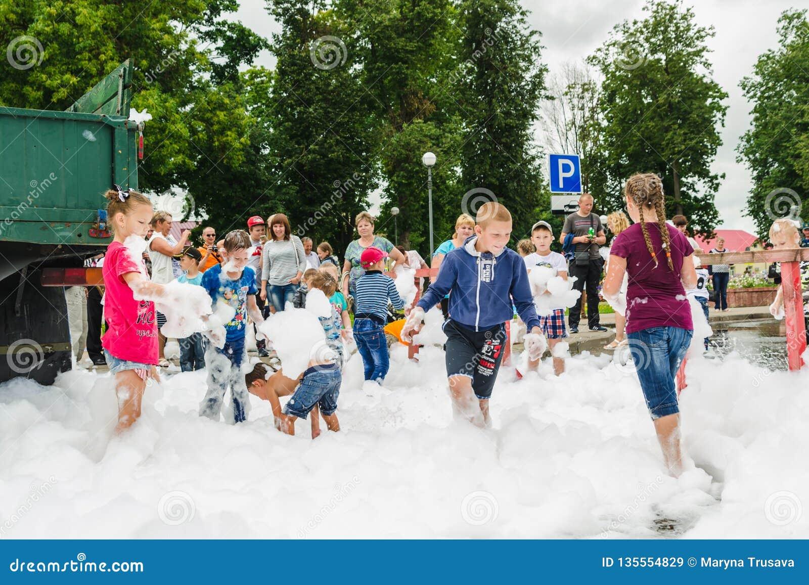 HORKI, БЕЛАРУСЬ - 25-ОЕ ИЮЛЯ 2018: Дети различных возрастов играют с воздушной белой пеной на празднике спасательной службы 112 м