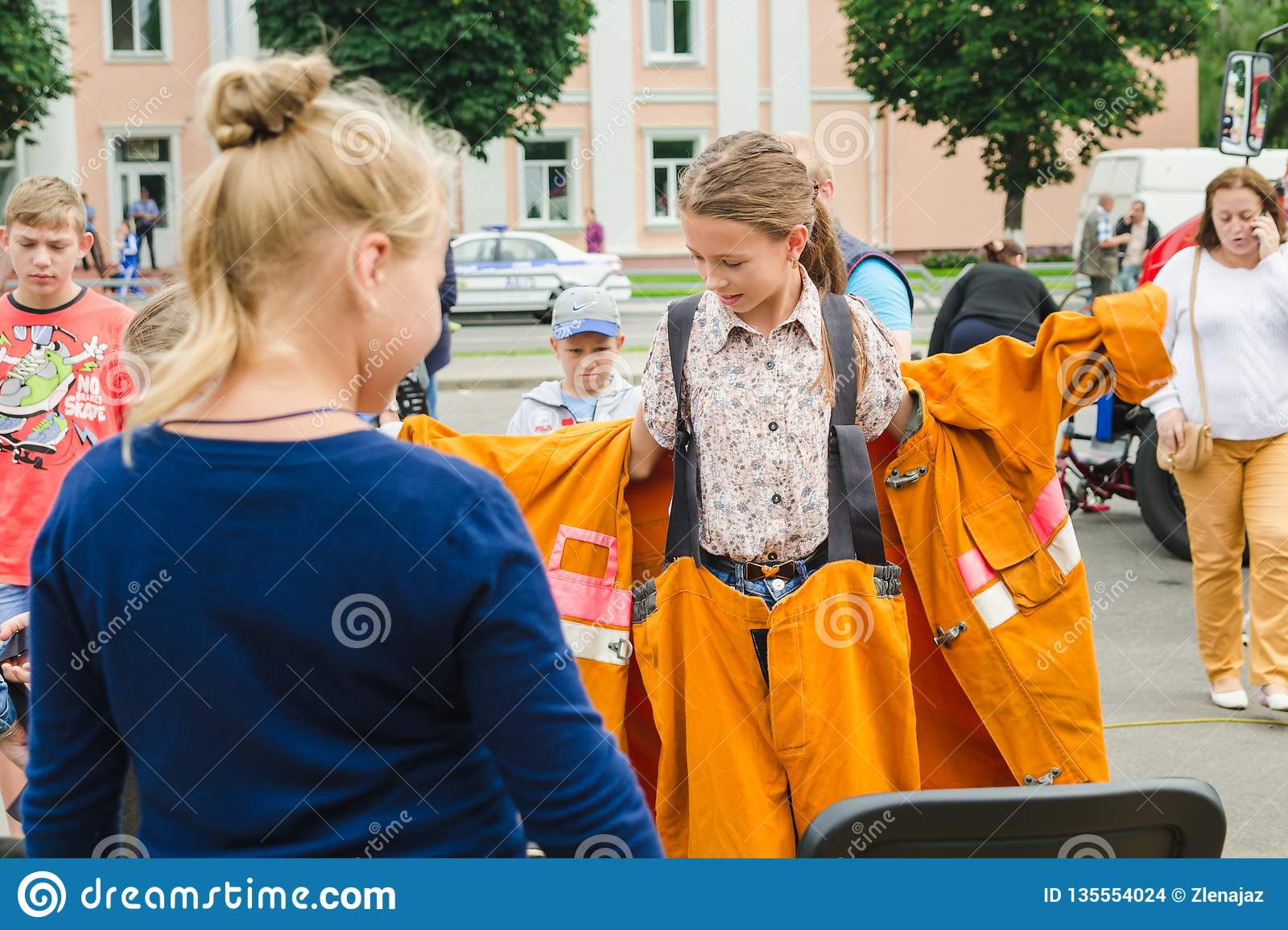 HORKI, BELARUS - JULY 25, 2018: Little blonde girl dresses an orange suit of the rescuer service 112 on a summer day in a crowd