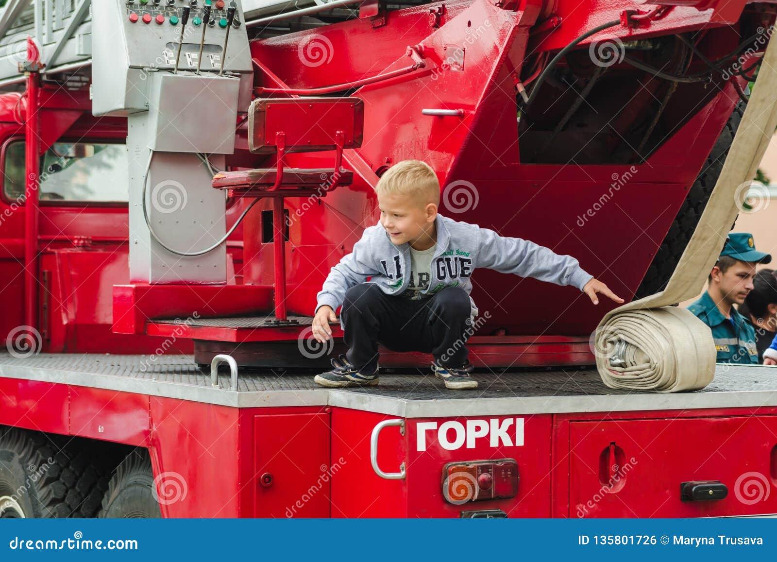 HORKI, BIELORRUSIA - 25 DE JULIO DE 2018: El muchacho juega en los coches rojos del servicio de rescate 112 en un día de fiesta e