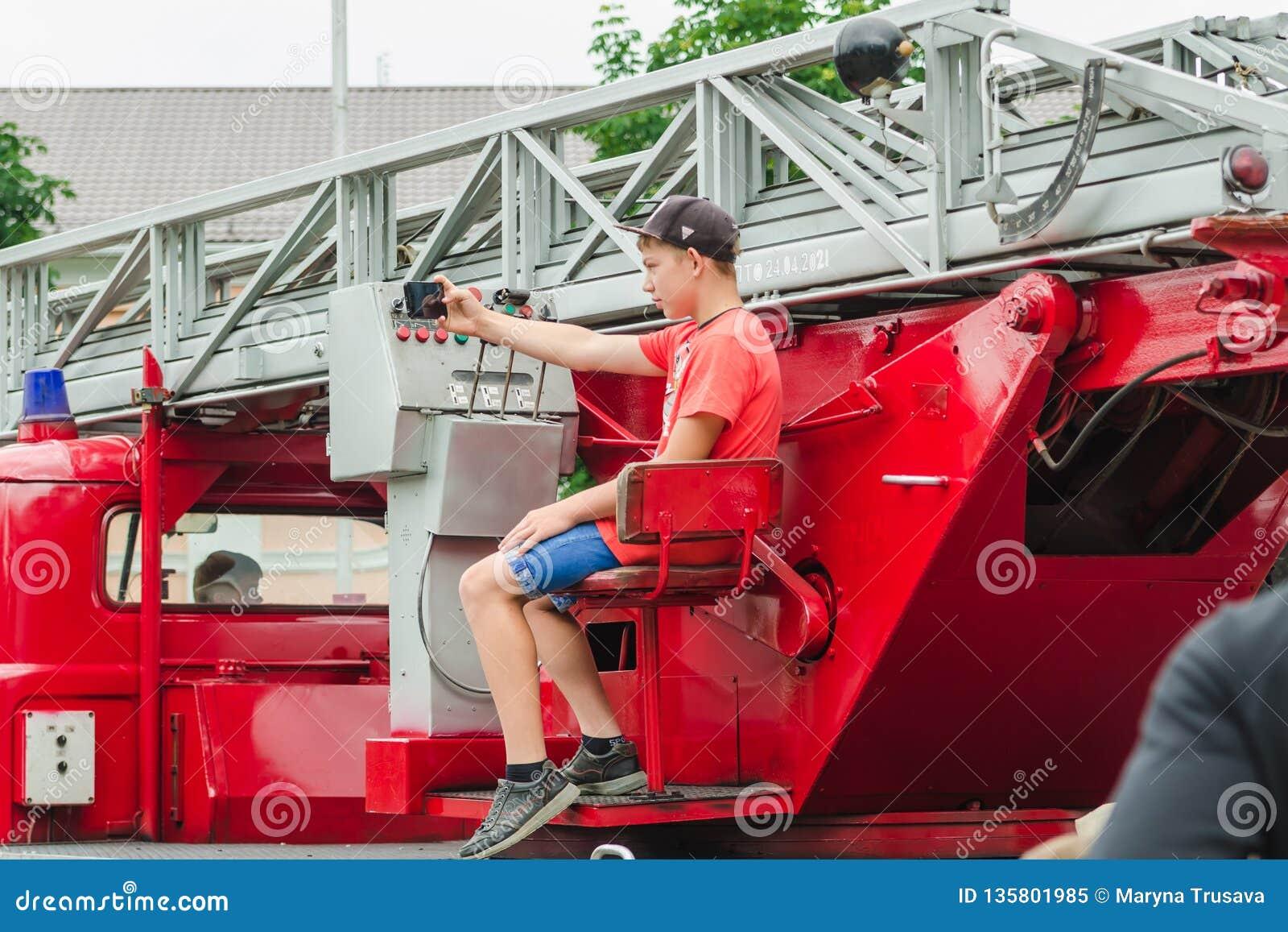 HORKI VITRYSSLAND - JULI 25, 2018: En pojke tar en selfie på en röd bilräddningstjänst 112 på en ferie i parkerar på en sommardag