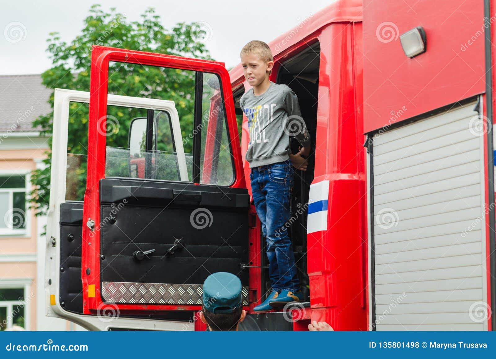 HORKI, WEISSRUSSLAND - 25. JULI 2018: Der Junge schaut aus dem roten Auto des Rettungsdiensts 112 an einem Feiertag im Park an ei
