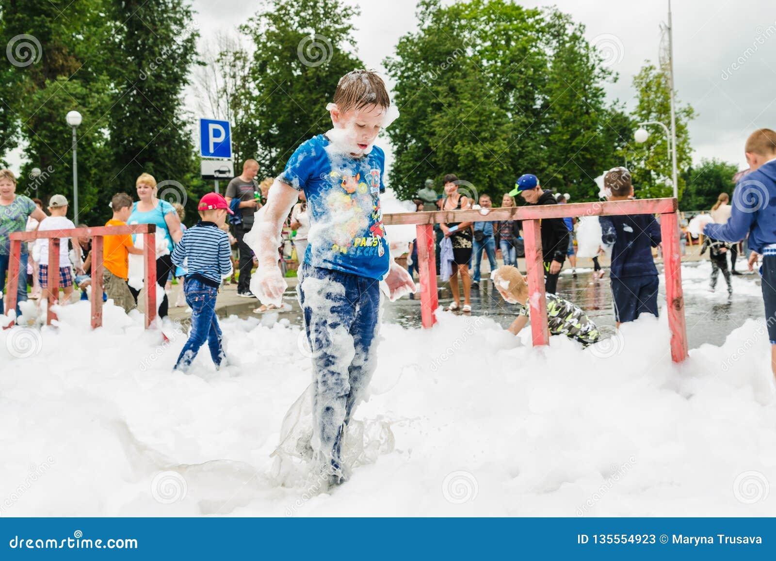 HORKI, WEISSRUSSLAND - 25. JULI 2018: Spiele eines wenig blonde Jungen mit luftigem weißem Schaum am Feiertag des Rettungsdiensts