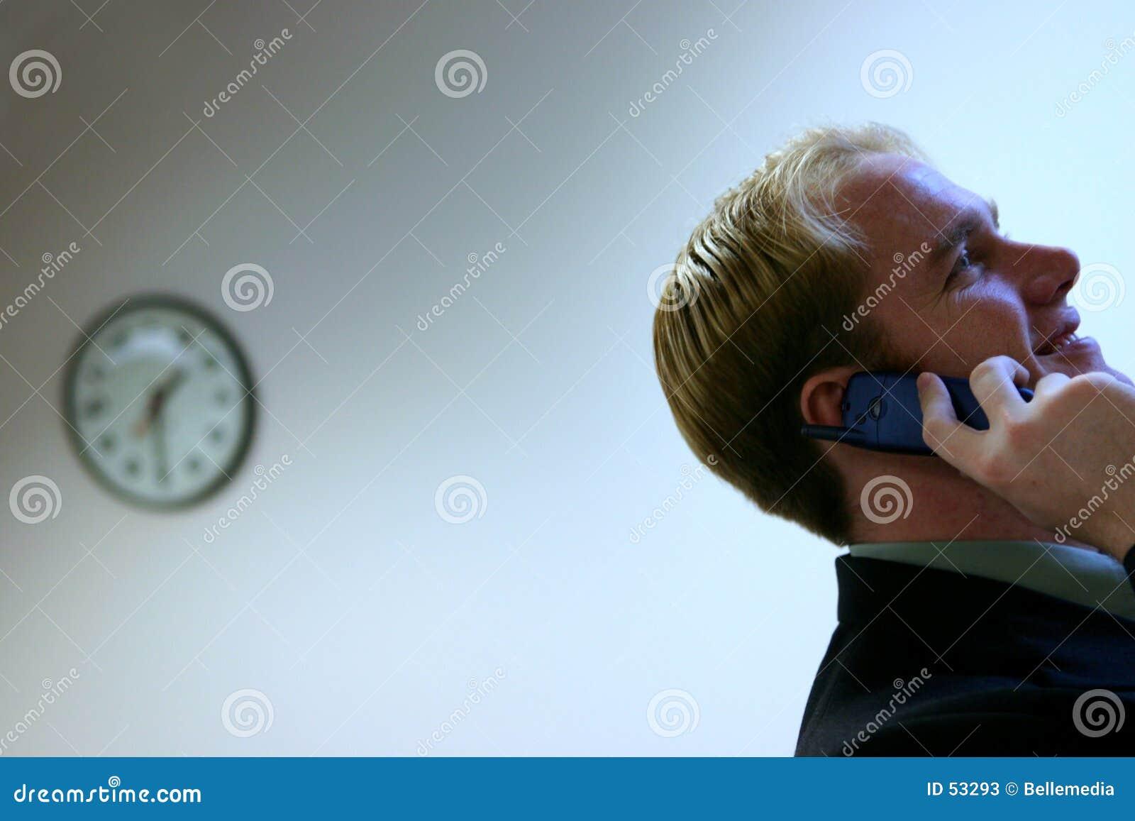 Horloge et jeune homme sur le portable
