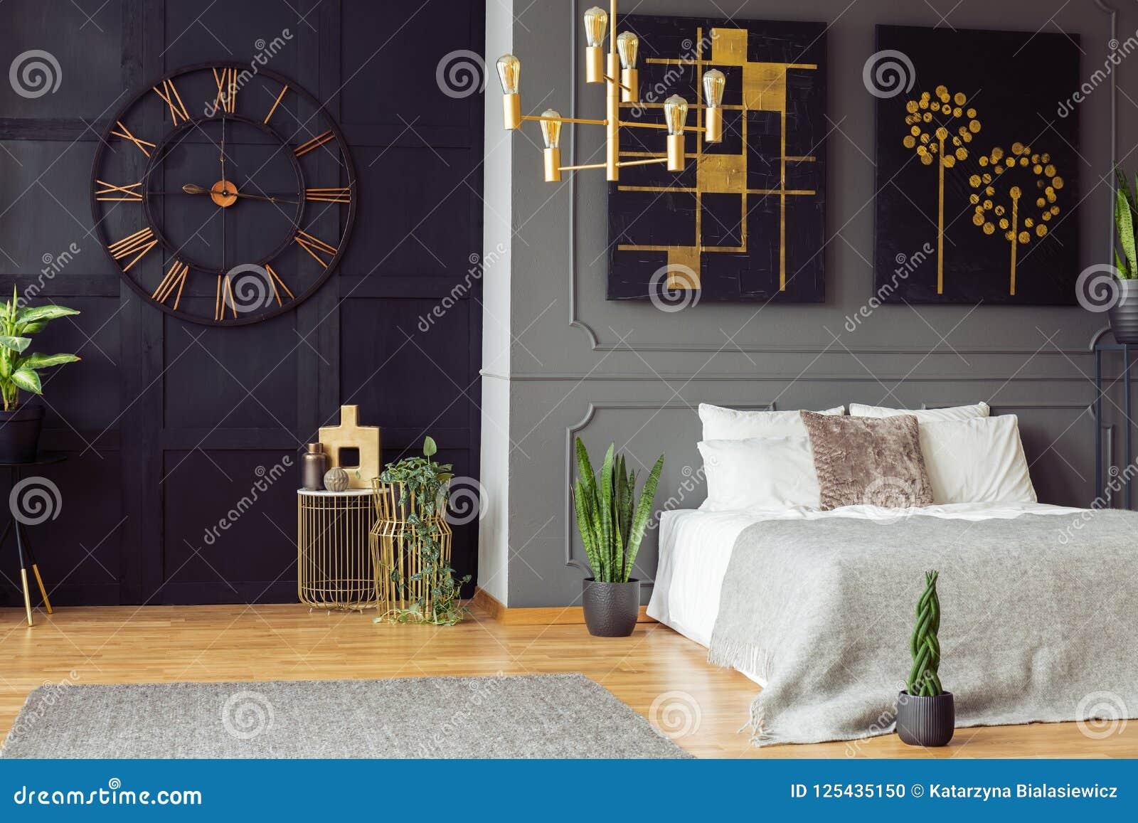Chambre Noir Blanc Et Or horloge noire, lustre d'or, peintures et lit blanc dans un