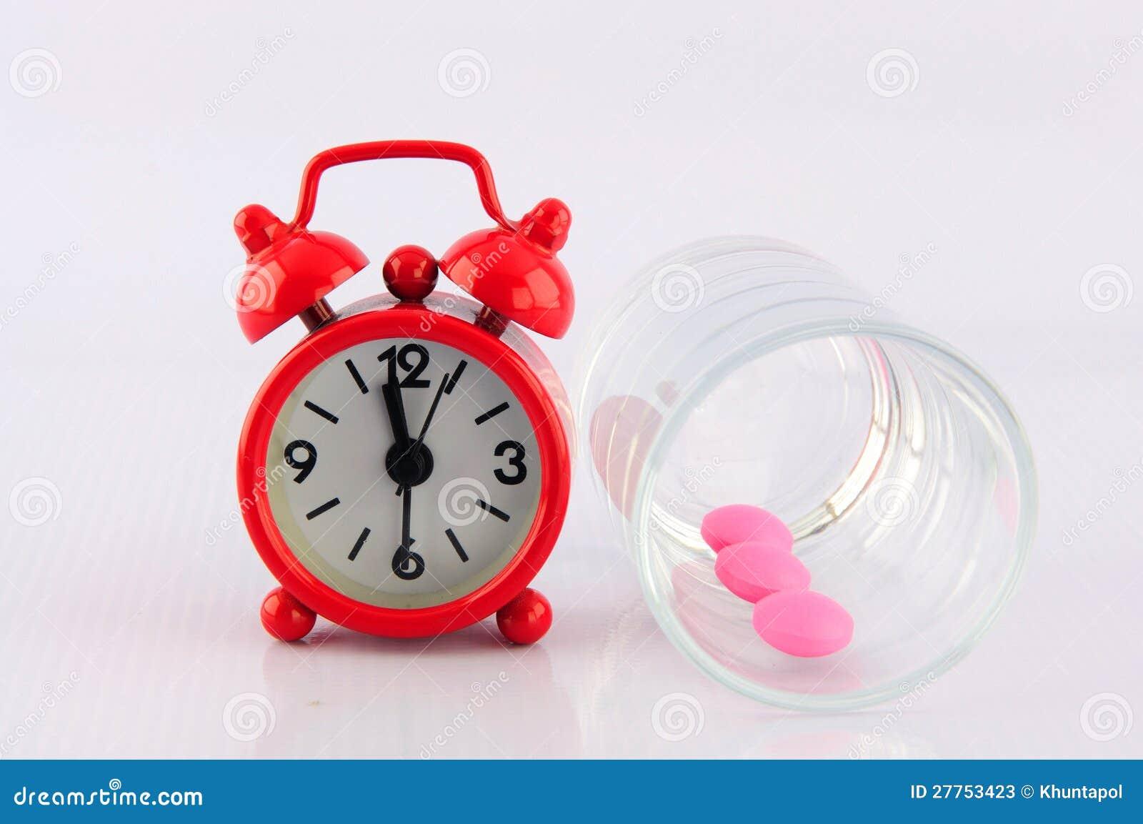 Horloge rouge et tablette rose en glace de dosage sur le fond blanc