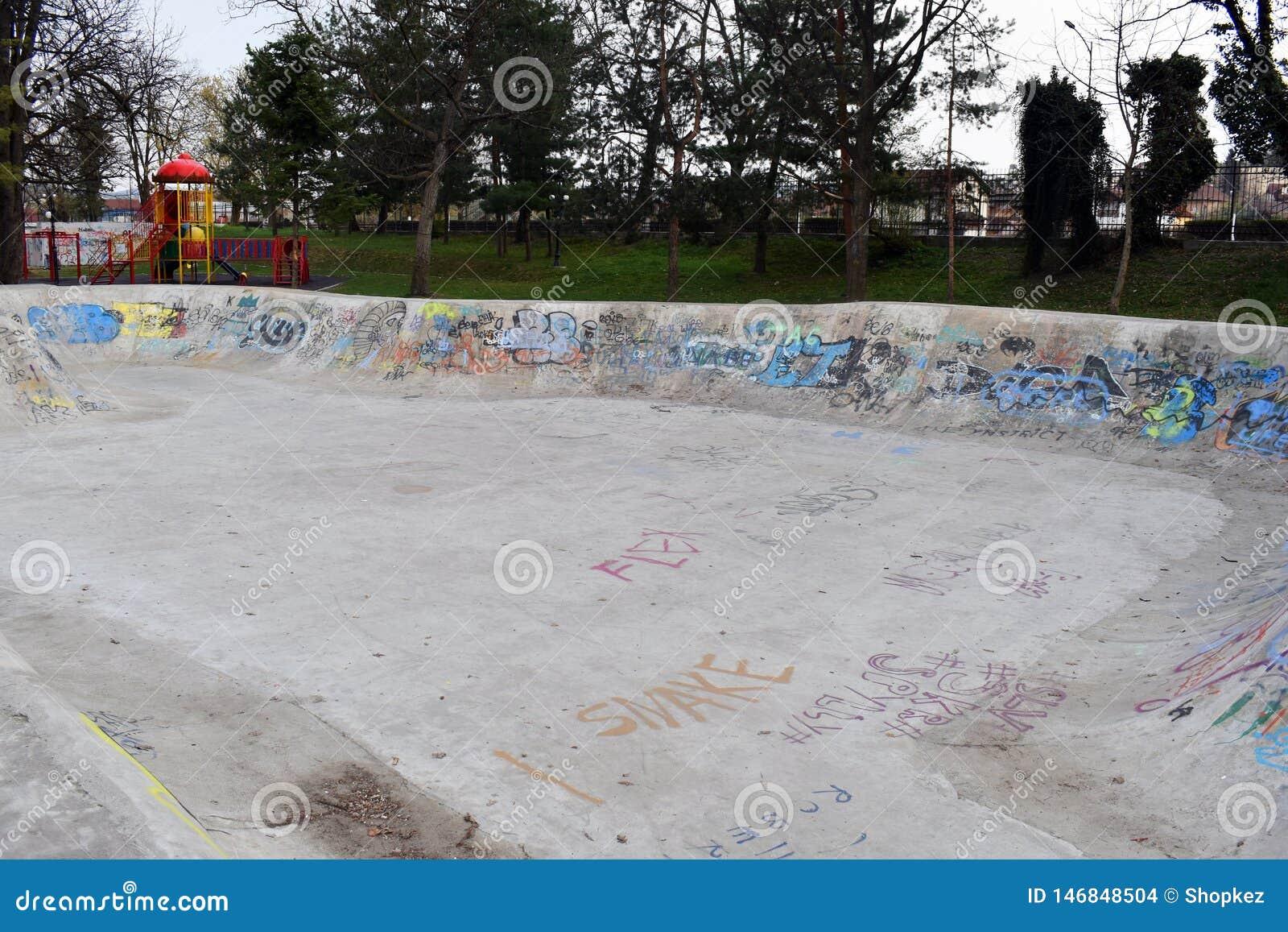 Hormigón vacío que anda en monopatín patinador del monopatín del diseño del skatepark del parque del patín con la pintada