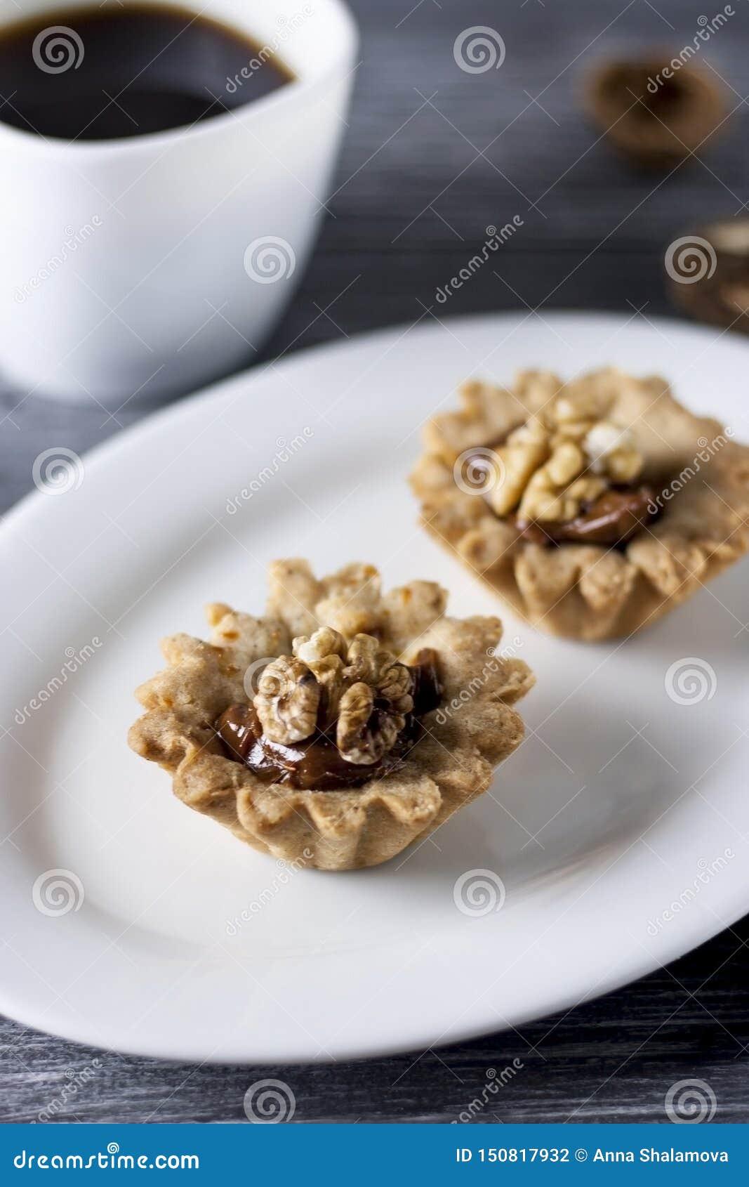 Hornada hecha en casa Cestas de la pasta de la torta de frutas con las nueces y la leche condensada