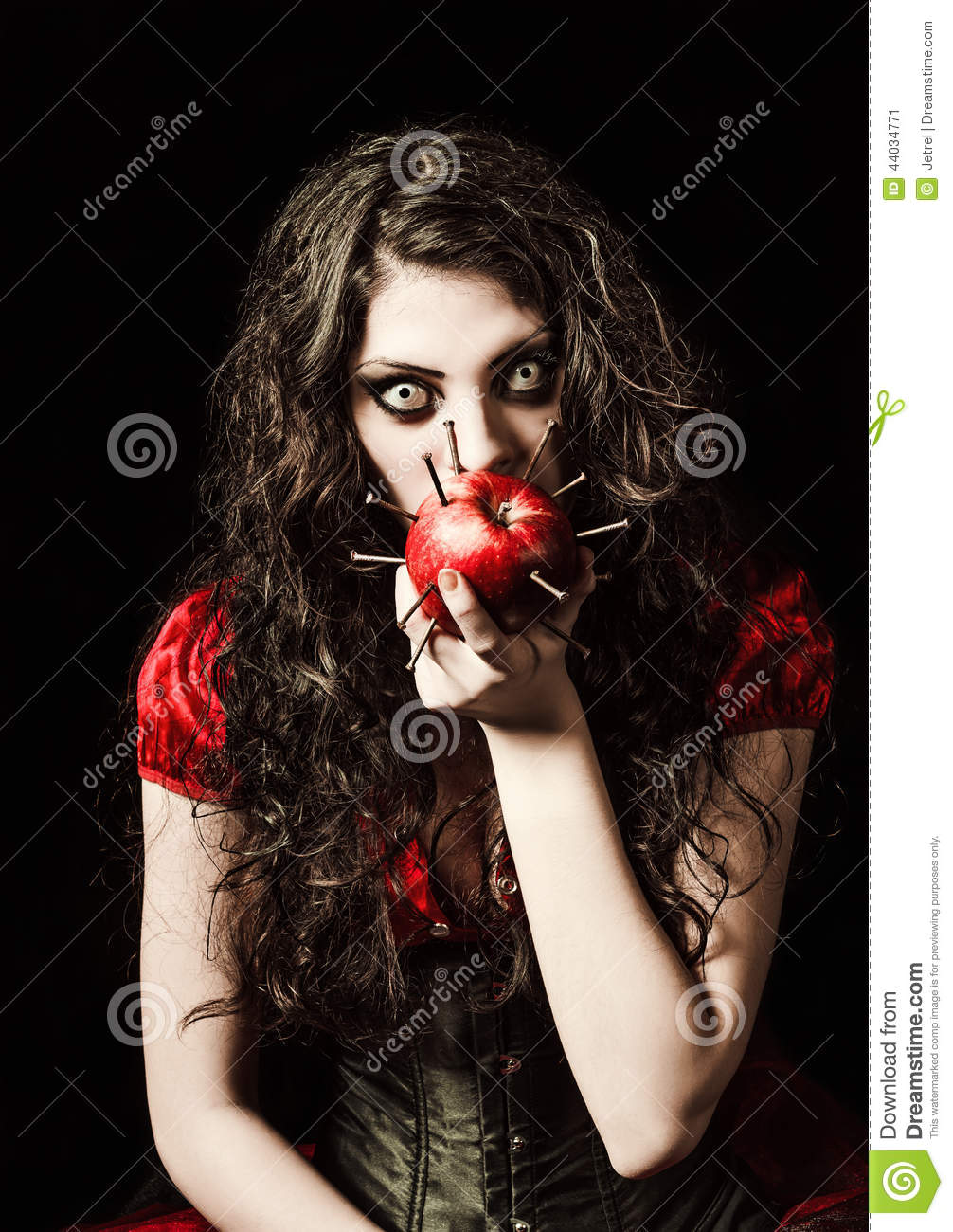Horror shot: strange scary girl eats apple studded with nails