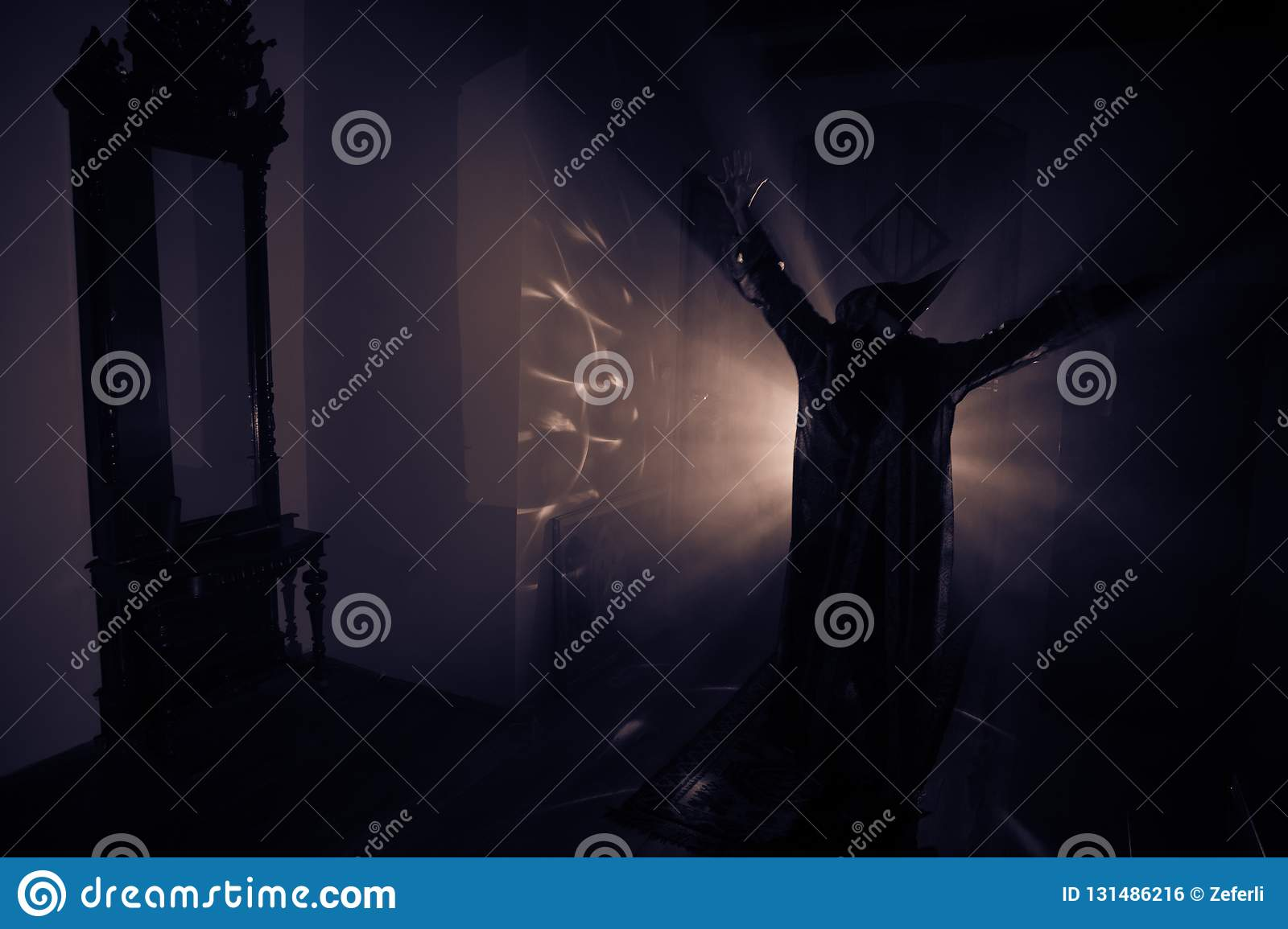 Horror silhouette of ghost inside dark room with mirror. Scary halloween concept. Silhouette of witch inside haunted house with