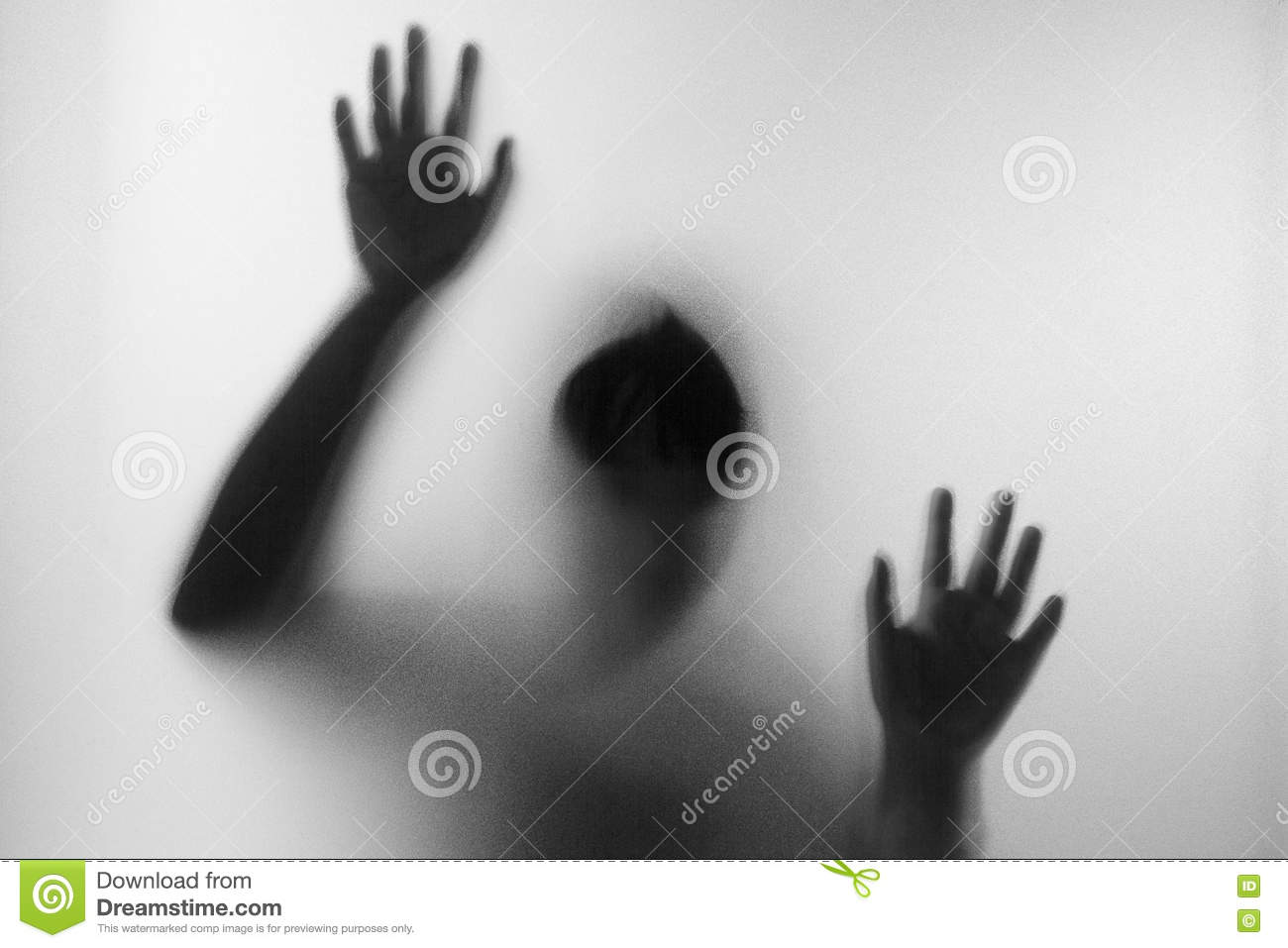 Horror woman behind the matte glass in black and white. Blurry hand and body figure abstraction.Halloween background.Black and