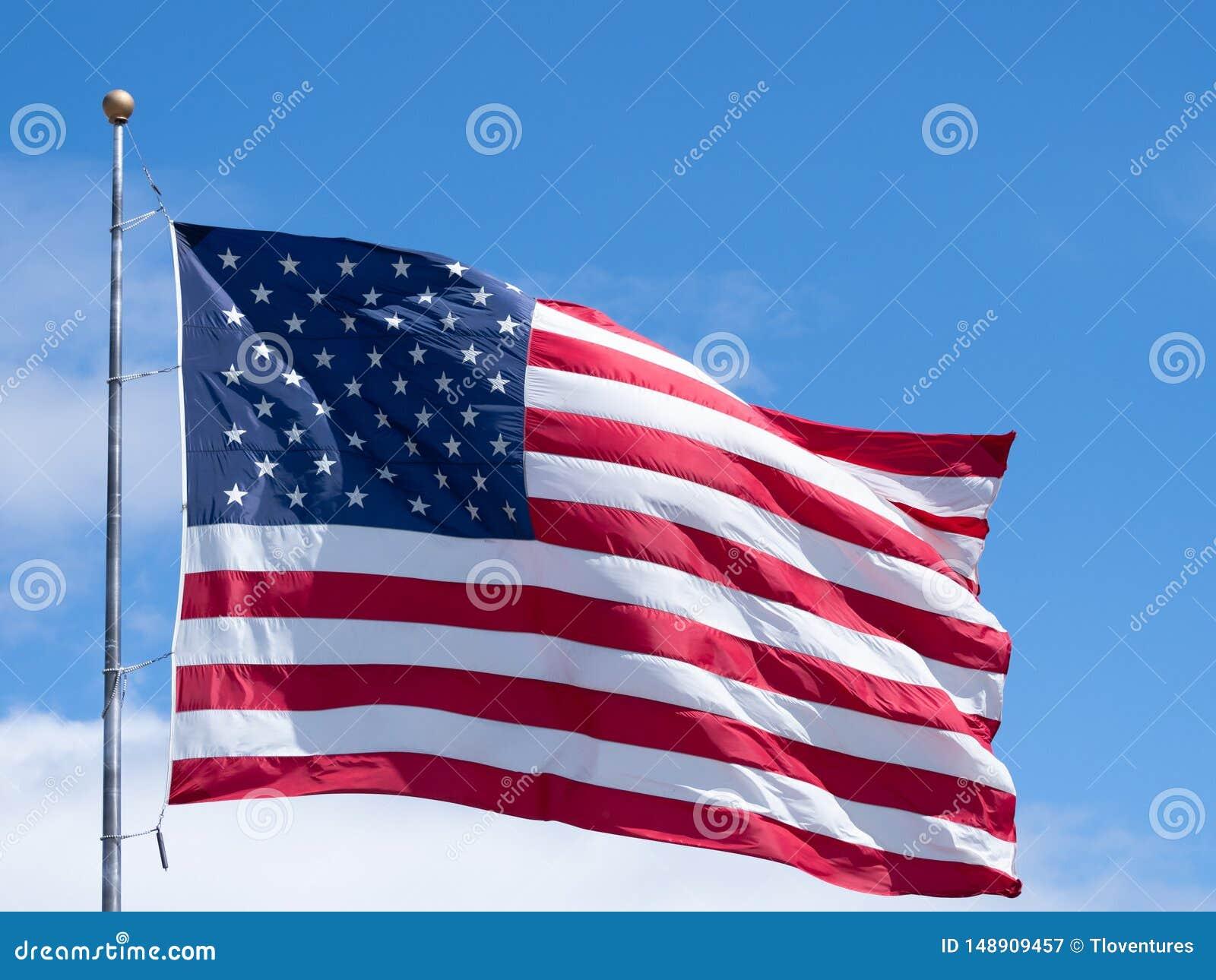 Horyzontalna Unfurled flaga ameryka?ska Przeciw niebieskiemu niebu z chmurami