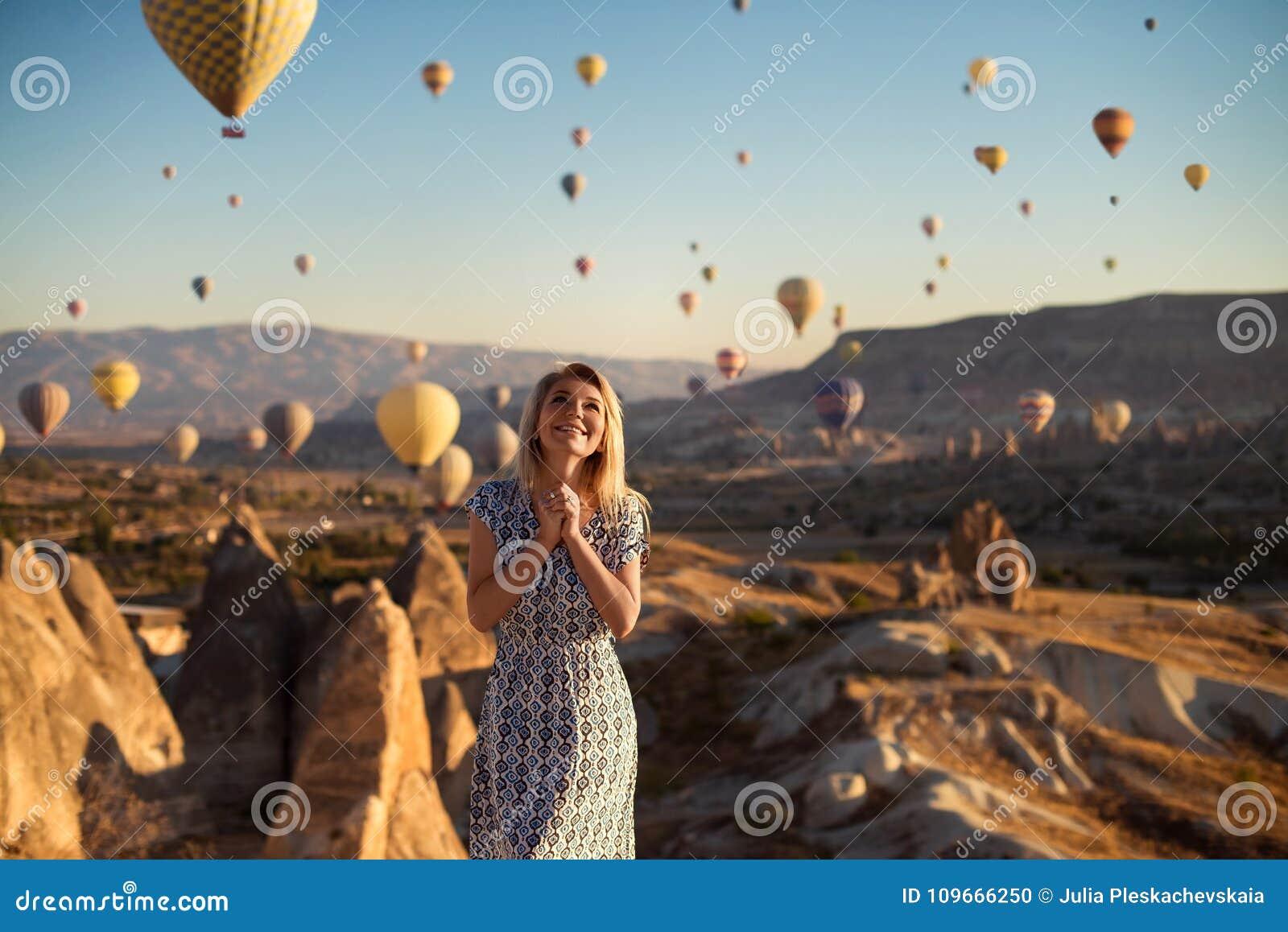 Horyzontalny plenerowy strzał szczęśliwej blondynki młoda uśmiechnięta kobieta w sukni excited jak stojaki na wysokich gór spojrz
