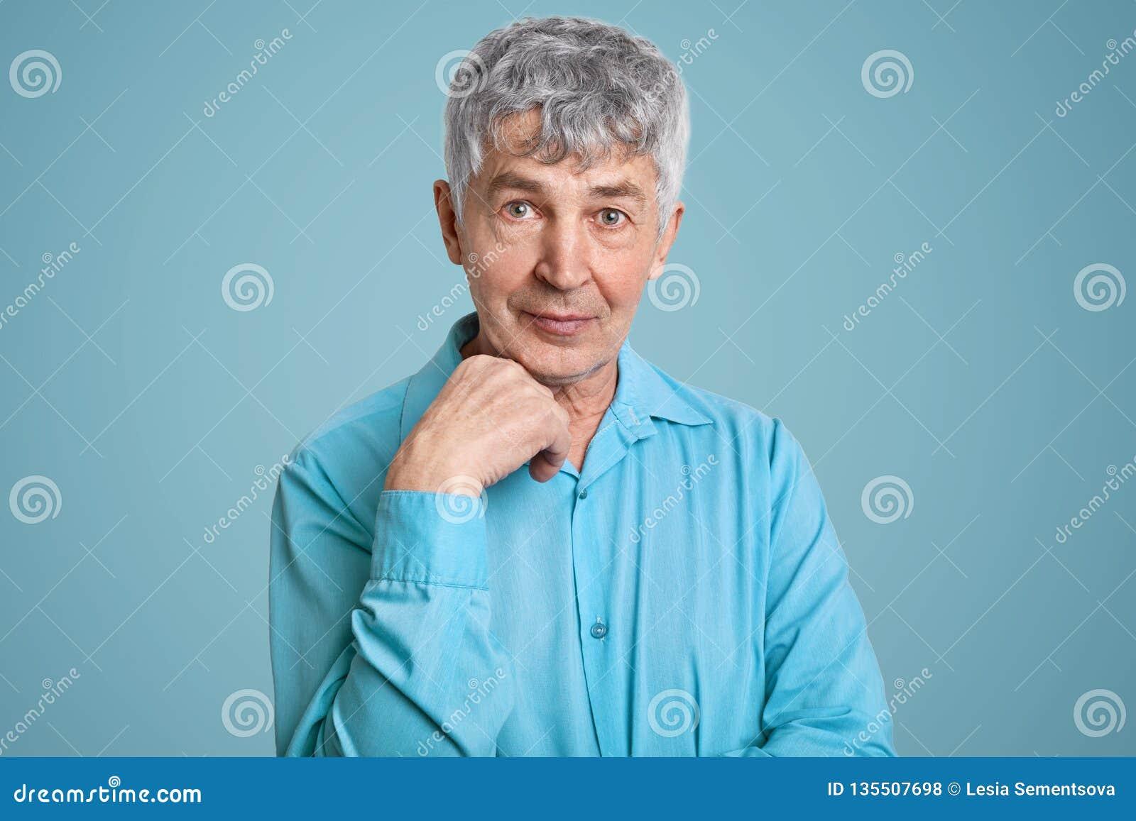 Horyzontalny strzał dojrzały popielaty z włosami Kaukaski męski emeryt jest ubranym elegancką koszula, utrzymanie ręka pod podbró