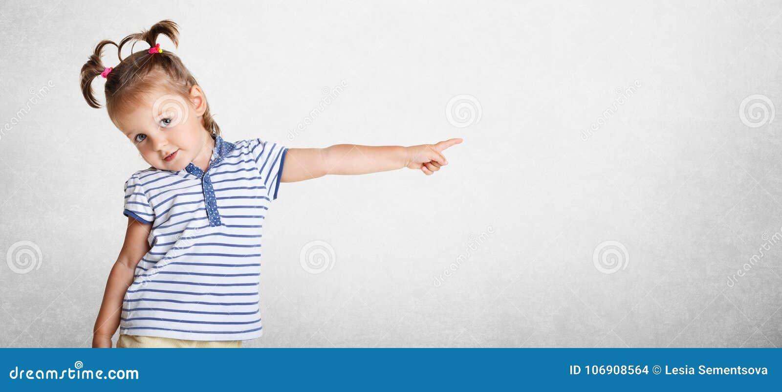 Horyzontalny strzał dosyć uroczy piękny mały dzieciak jest ubranym pasiastą t koszula, śmiesznego dwa konika ogonu, wskazuje z je