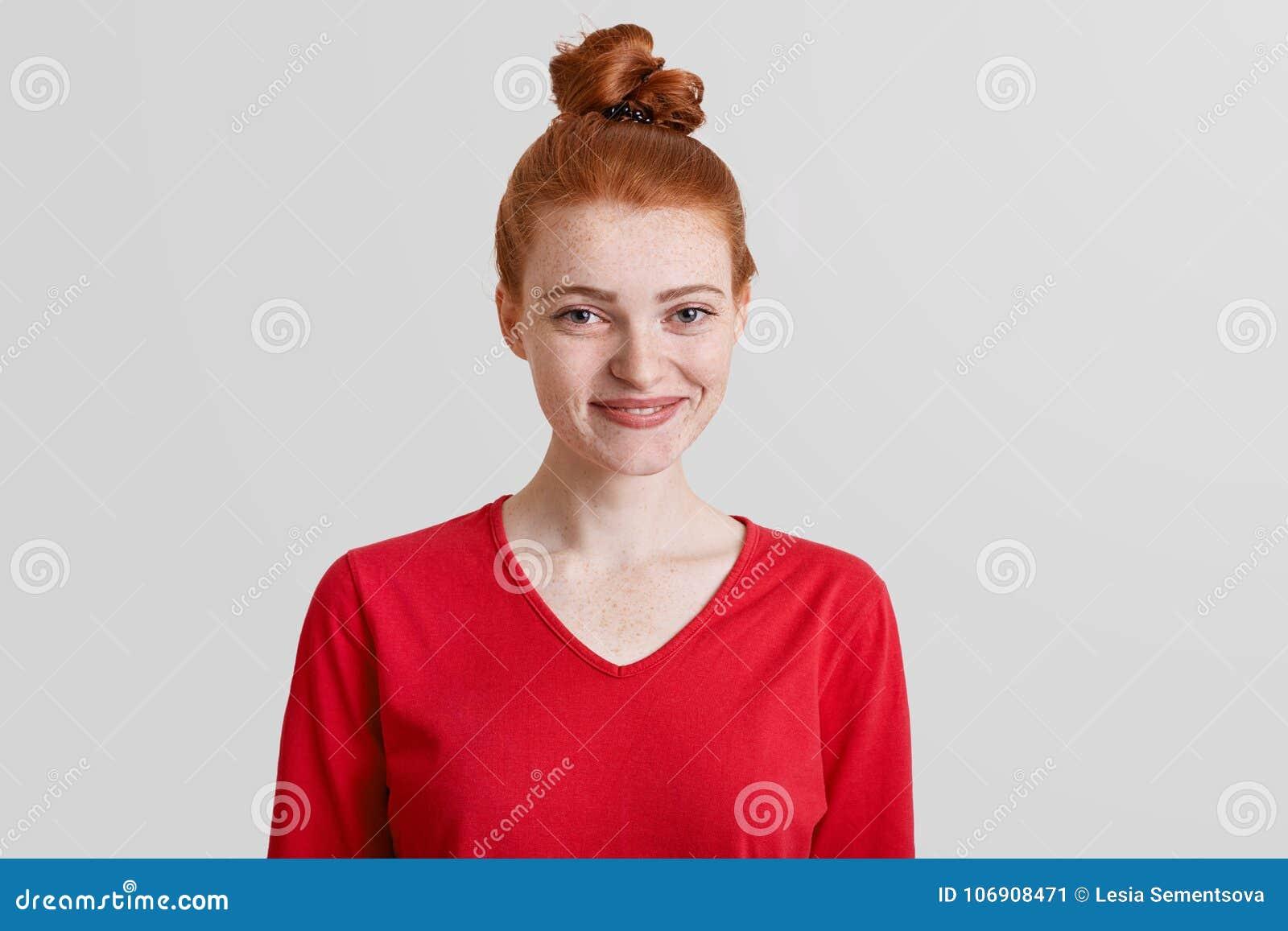 Horyzontalny strzał nieśmiała zadowolona piegowata młoda kobieta z imbirową włosianą kępką, ubierający w czerwonym pulowerze nad