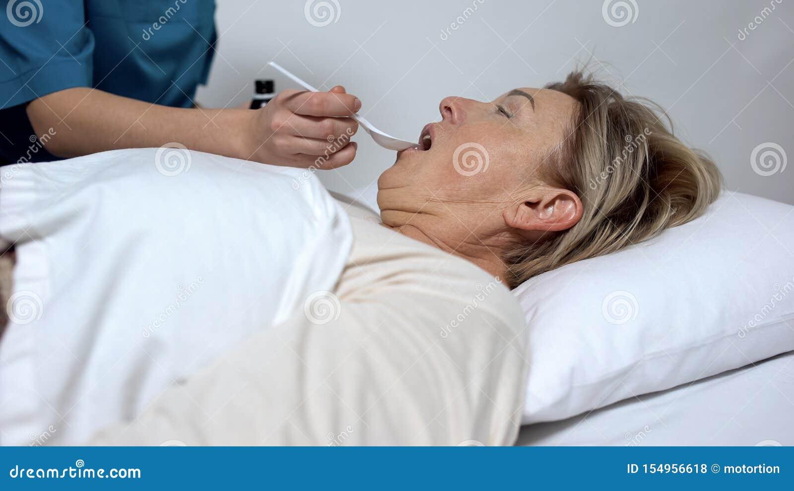 Hospicjumu pracownik daje laxative syropowi niepełnosprawna kobieta, traktowanie i terapia,