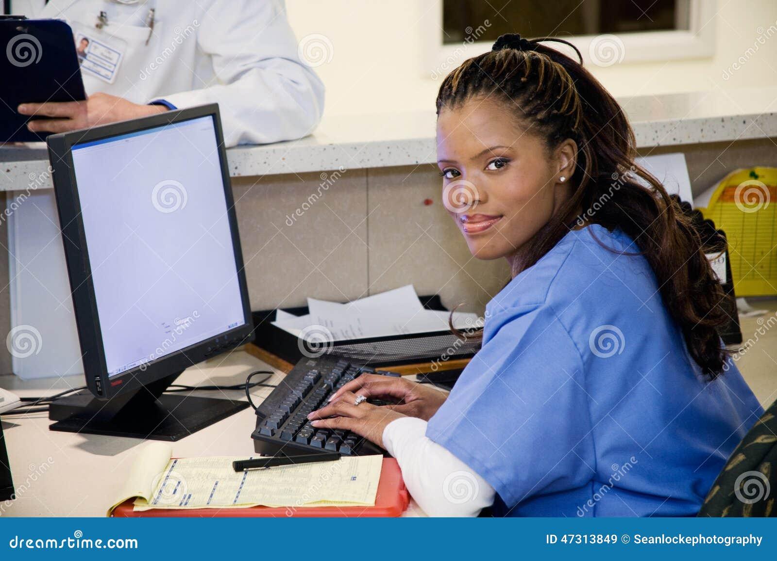 Hospital: Enfermeira de sorriso na estação de trabalho da clínica