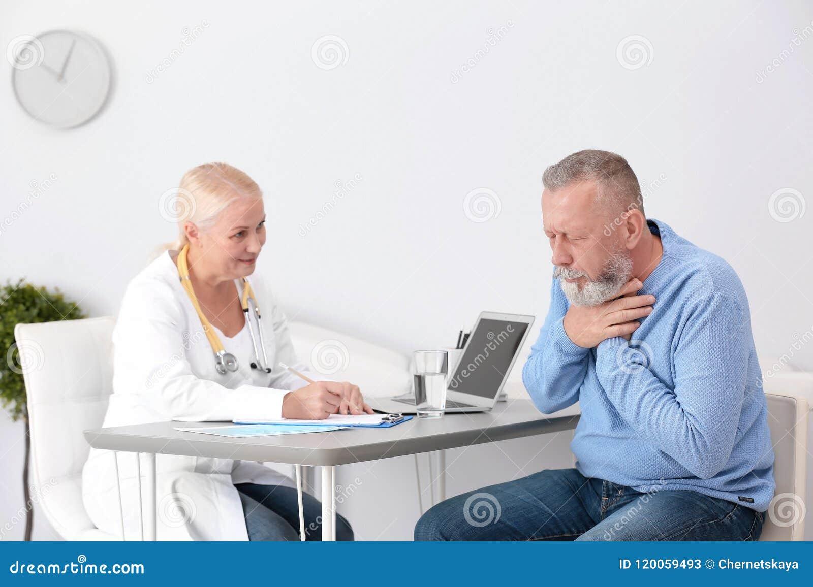 Hostande mogen man som besöker doktorn