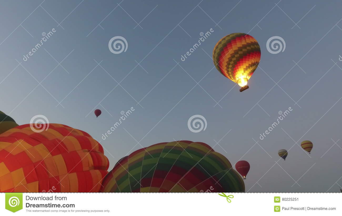 Hot Air Balloons Ascend Into The Sky From Parking Lot In