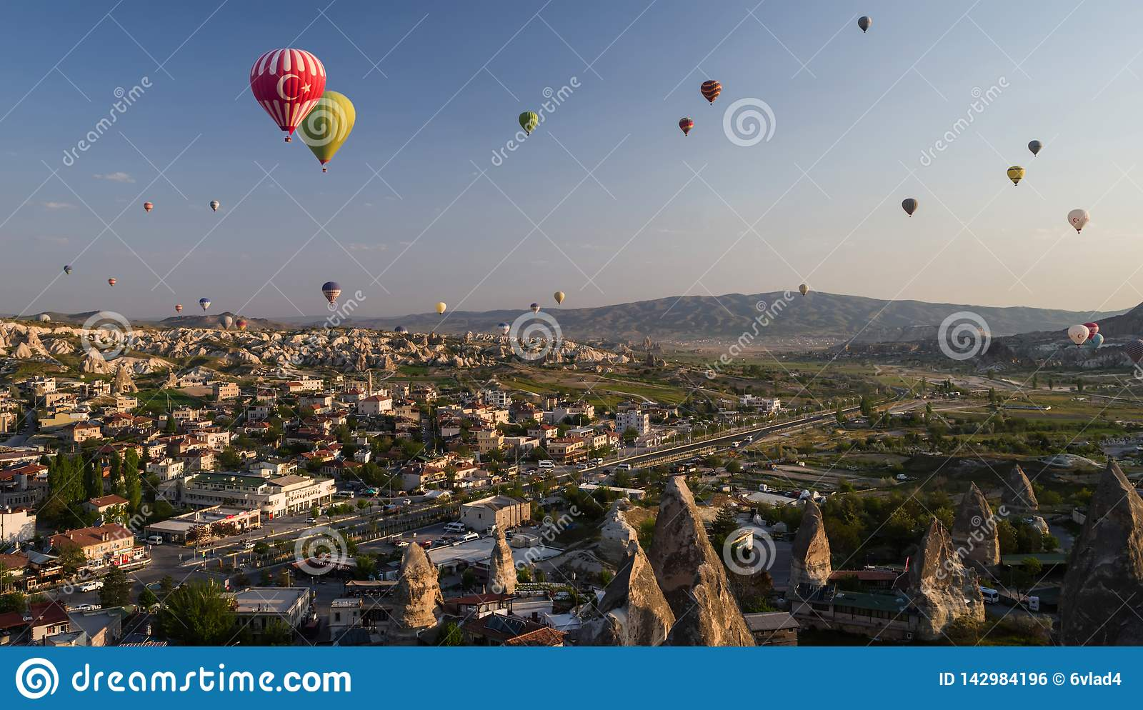 Hot air balloons flying over Goreme at sunrise with sandstone formations in the foreground