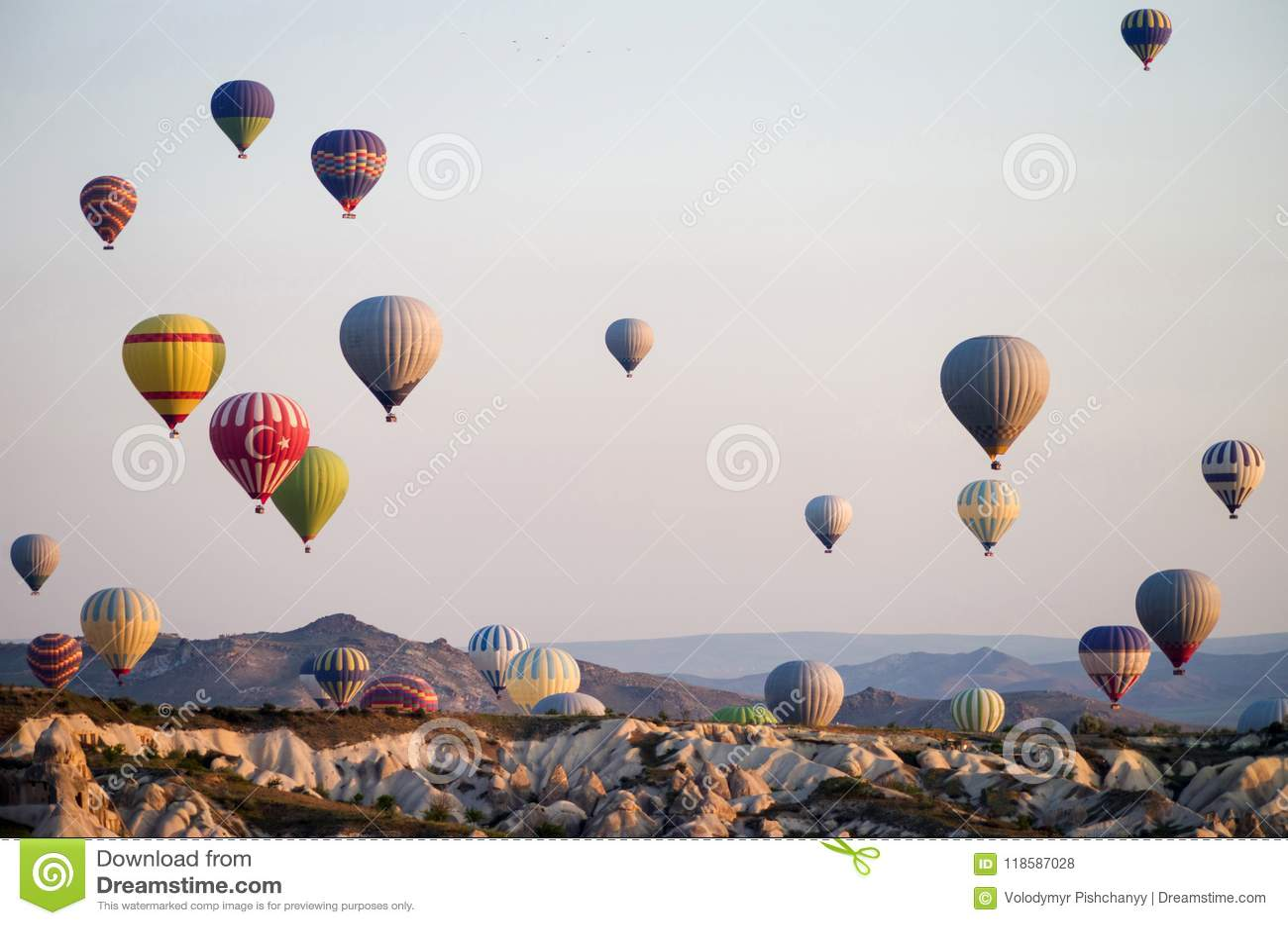 Hot air balloons at sunrise flying over Cappadocia, Turkey. A balloon with a flag of Turkey