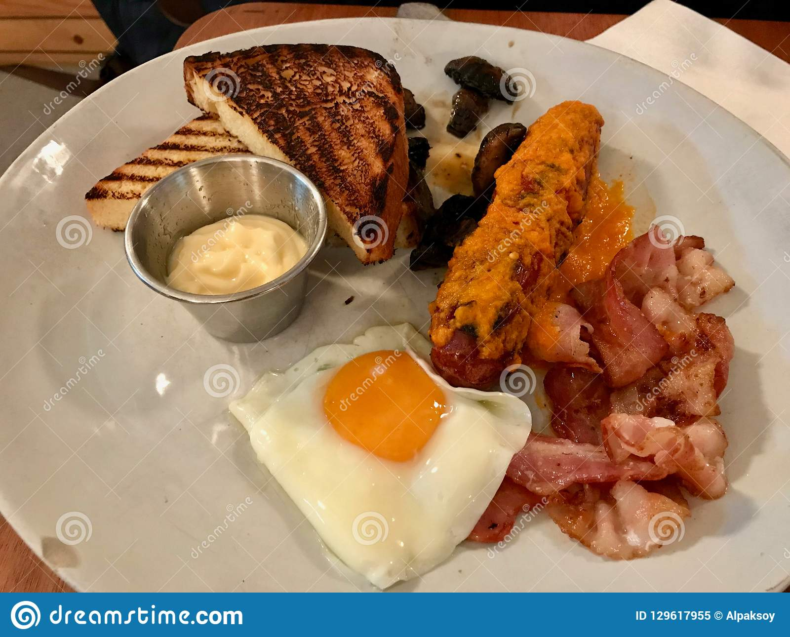 Hot Breakfast Plate With Sausage Fried Egg Bacon And Toast Bread