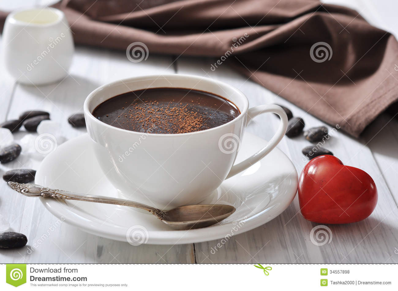 ... in cup with cocoa powder and red stone heart on wooden background