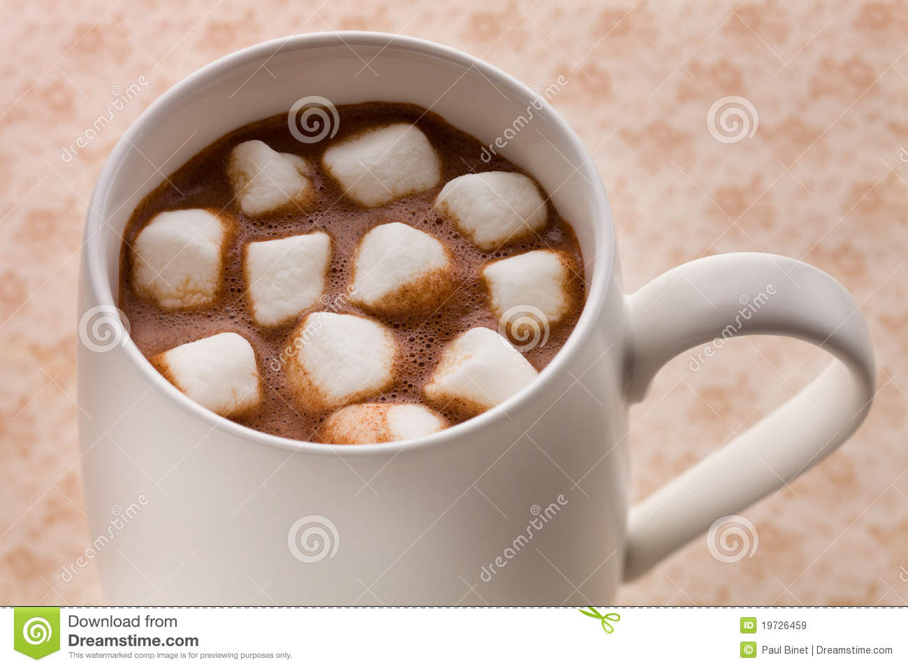 Hot chocolate drink from above on a brown background with marshmallow.