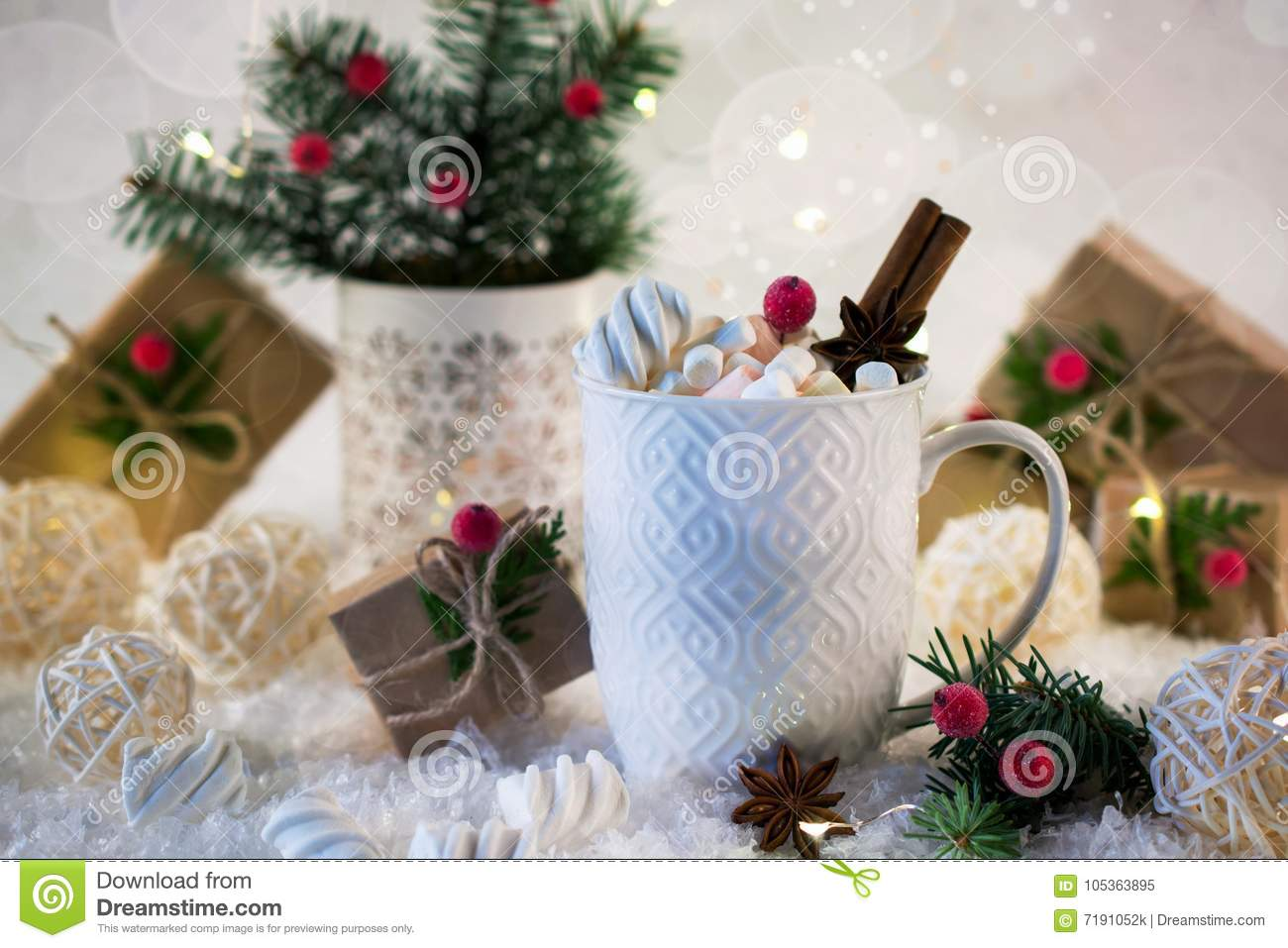 hot chocolate in a white cup with marshmallows and christmas gifts on the bright light background