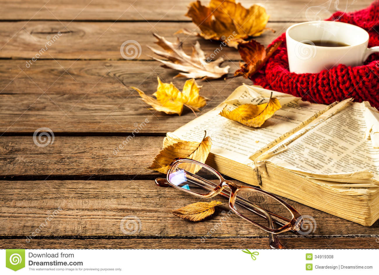 Hot coffee, book, glasses and autumn leaves on wood background