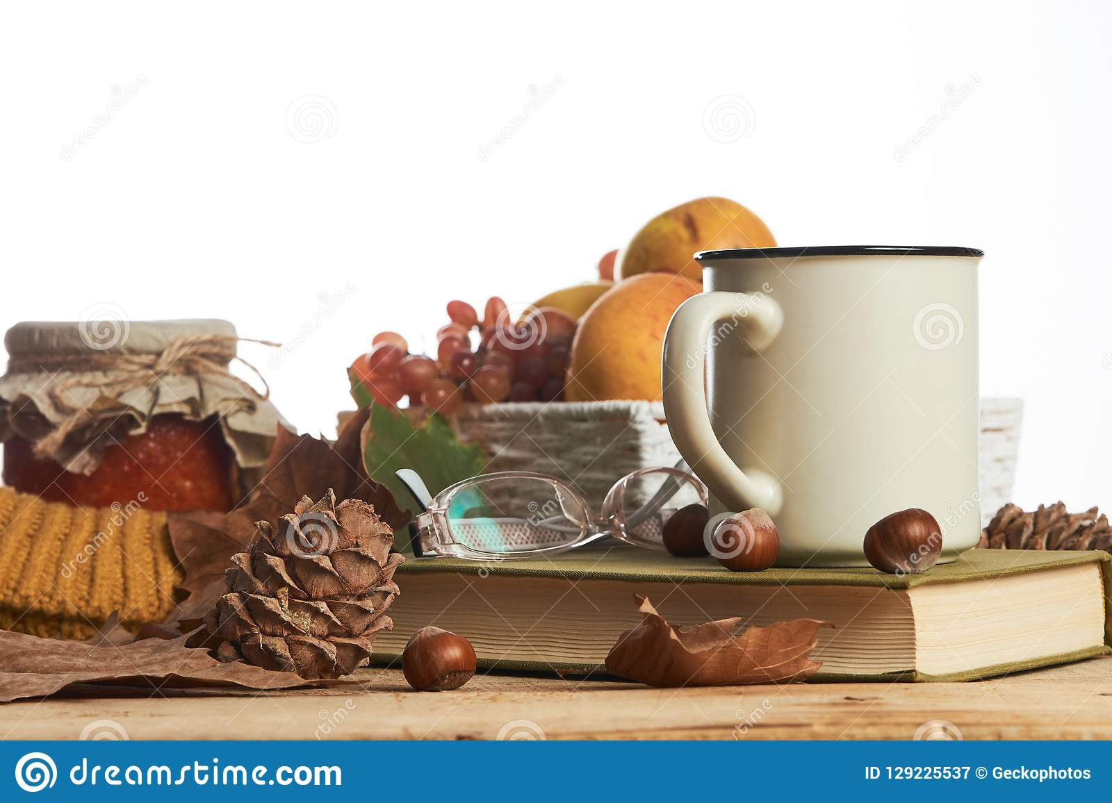 Hot coffee cup old book glasses and autumn leaves with fruit basket