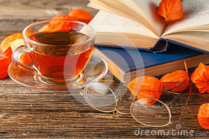 Hot coffee, vintage book, glasses and autumn leaves on wood back