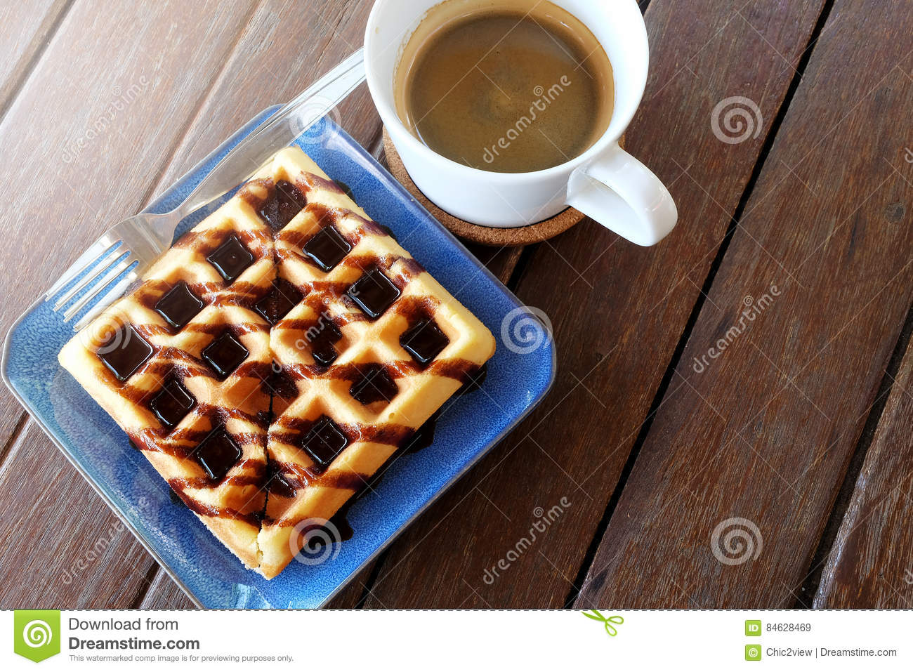 Hot coffee and Waffles with chocolate sauce on wooden table background.