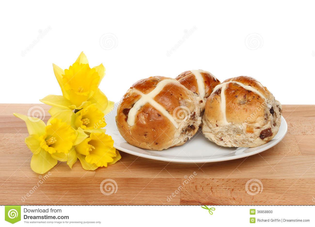 Hot cross buns and daffodils on a wooden table against a white ...