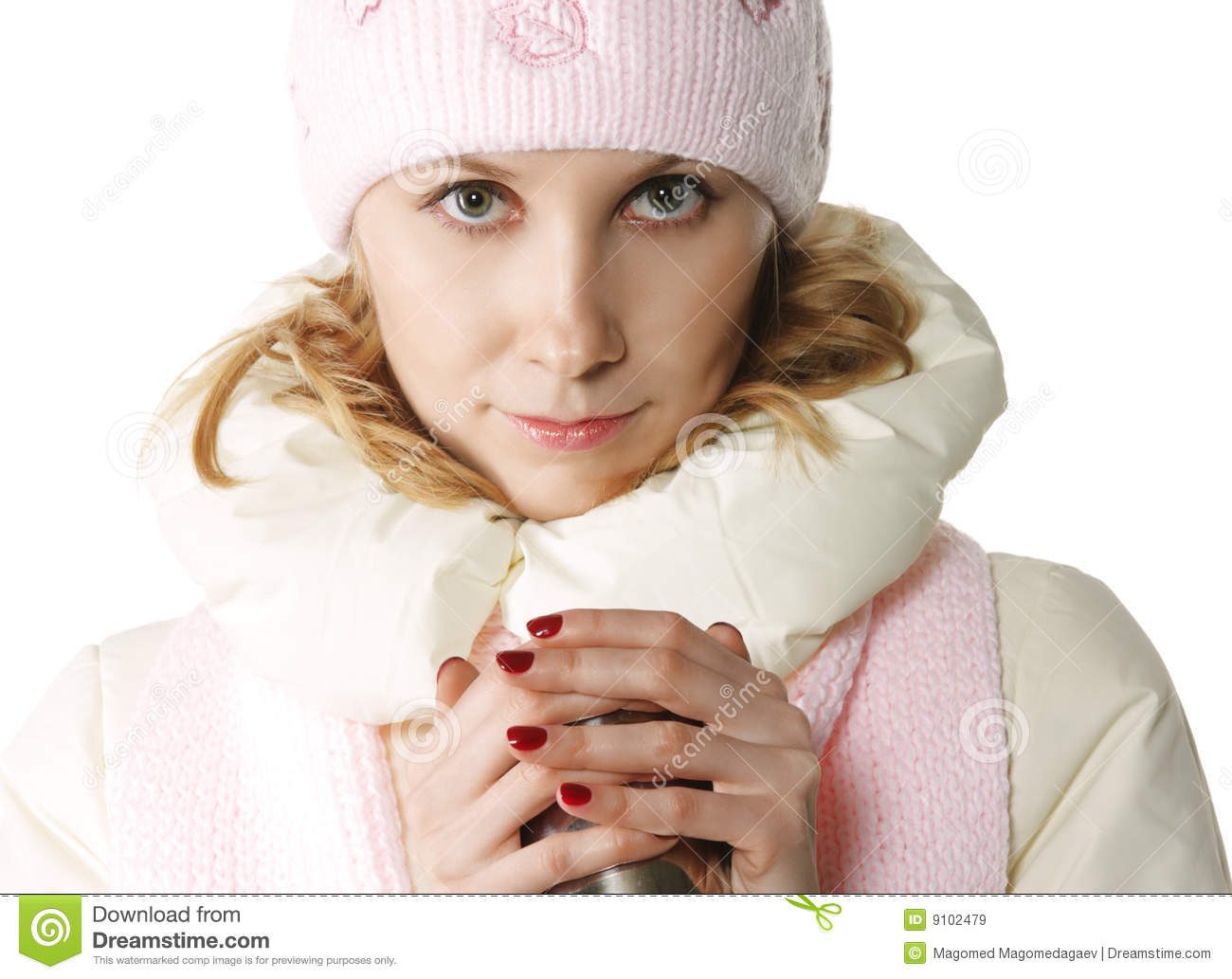 ... young woman in winter clothes warming hands with cup of hot drink