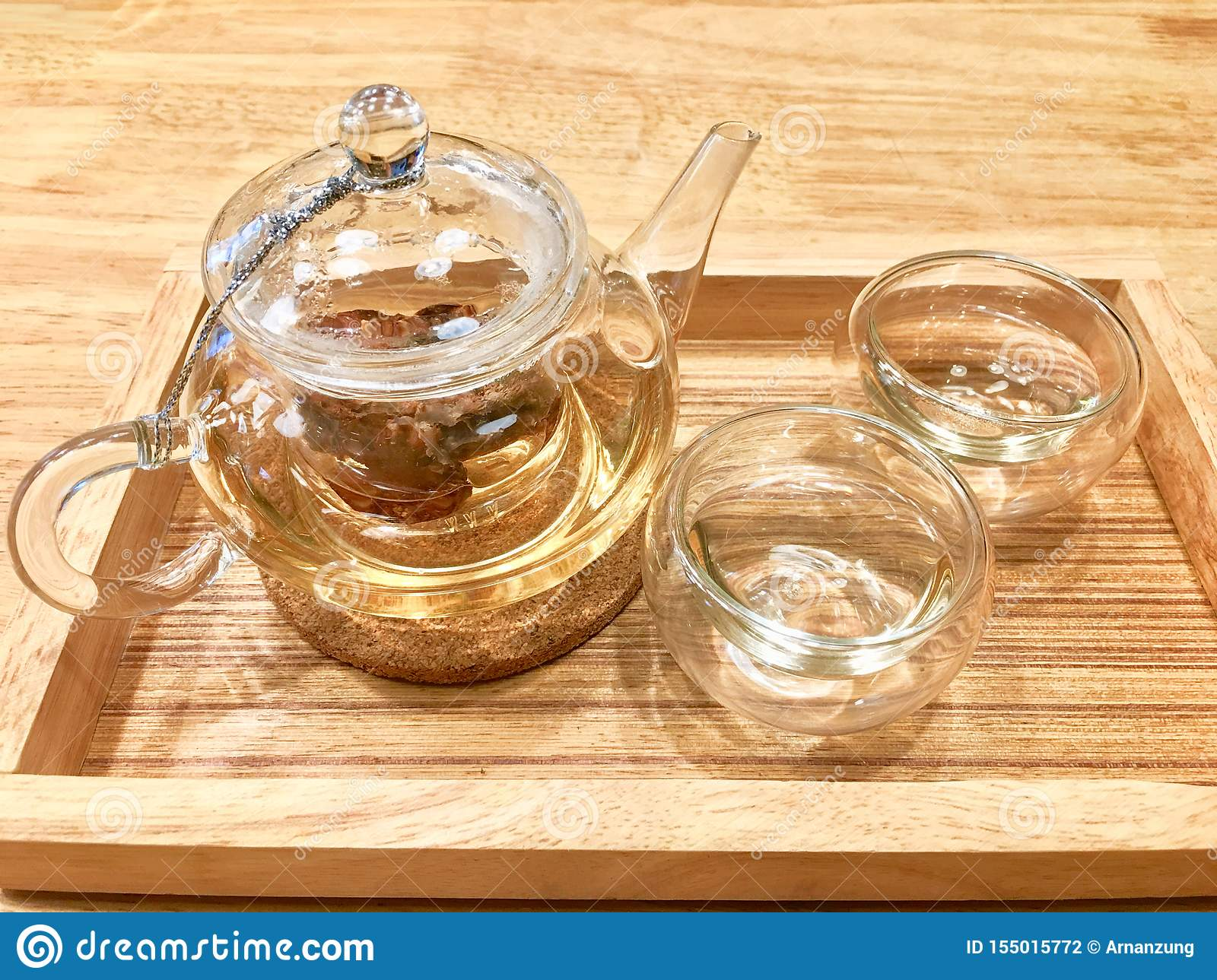 Hot herbal tea inside transparent cup and glass jar on the light brown wooden tray put on wooden table.